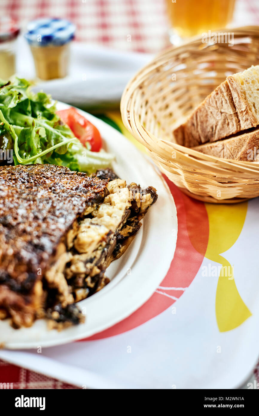 A rustic wild mushroom frittata with fresh bread on a French cafe table top in the Dordogne France - Stock Image