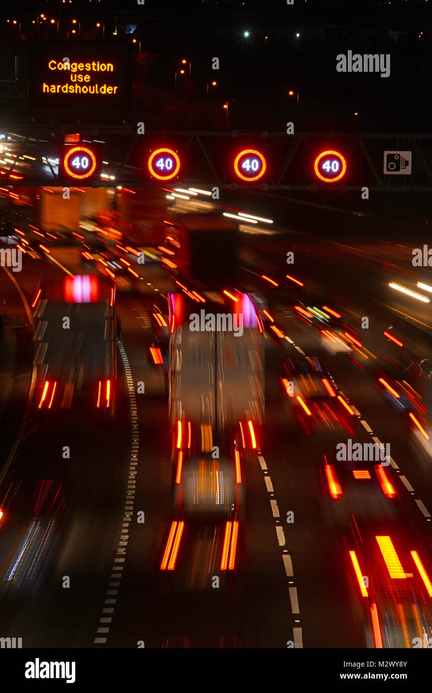 traffic jam by reduced speed limit and speed camera warning signs and speed on the m62 motorway leeds at dusk yorkshire - Stock Image
