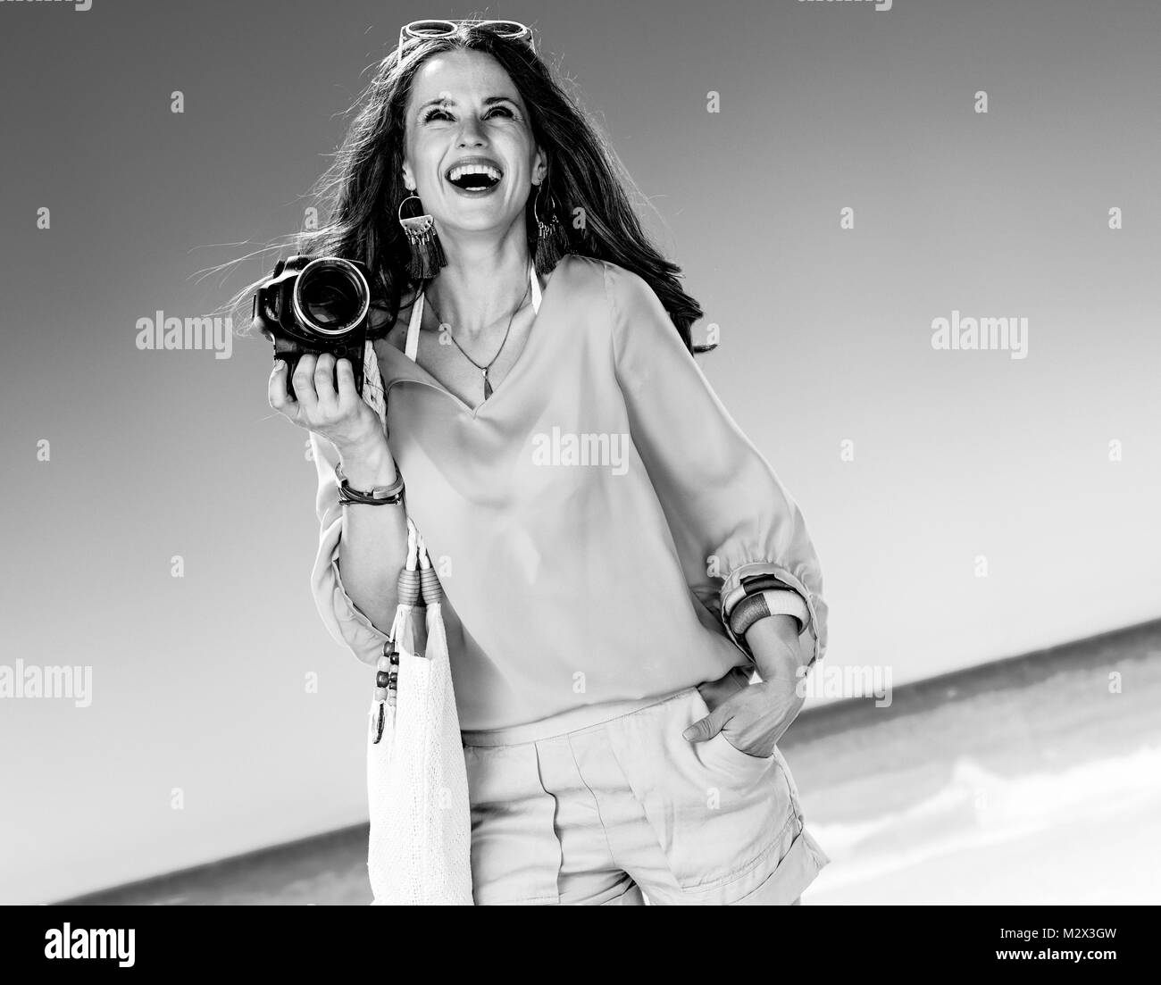 Perfect summer. smiling young woman in shorts and yellow blouse with white beach bag on the beach with digital SLR - Stock Image