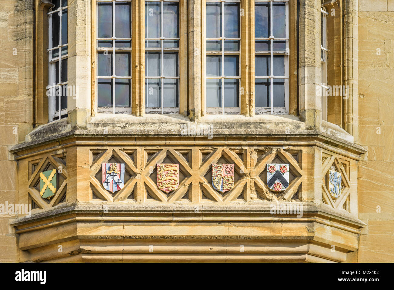 Carved stone emblems on a streetside window of Oriel college at the university in the city of Oxford, England. - Stock Image