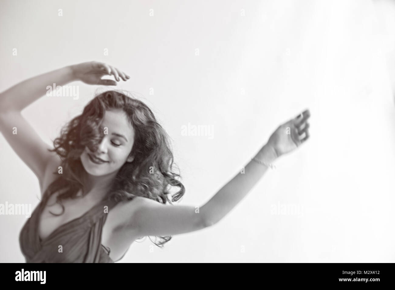 Beautiful classically dressed young girl dances across a grey backdrop isolated. Long dress and long hair monotone - Stock Image
