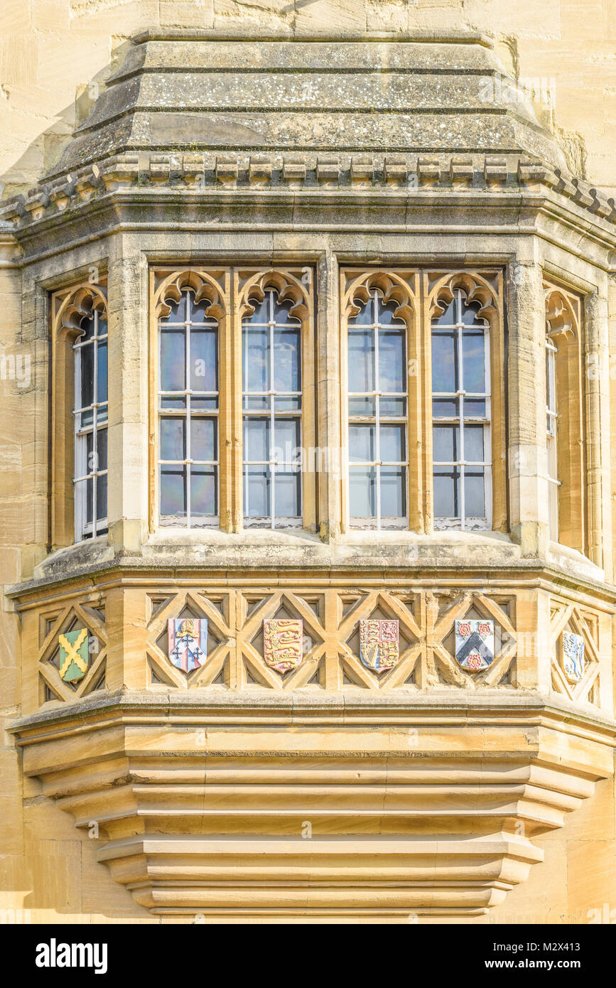 Ornate streetside window with emblems of Oriel college at the university in the city of Oxford, England. - Stock Image