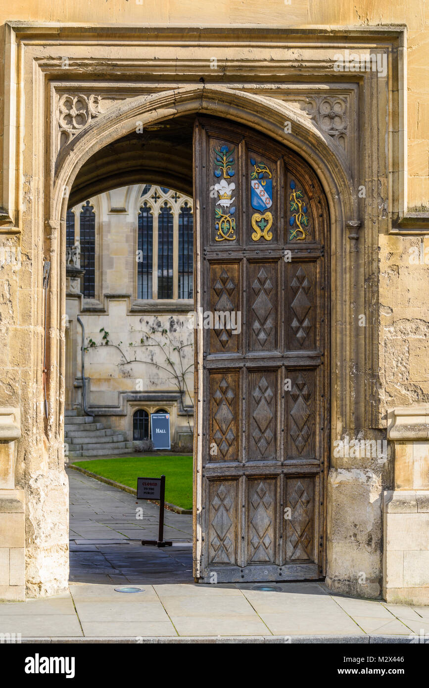 Carved wooden emblems on the door of the main entrance to Oriel college at the university in the city of Oxford, - Stock Image