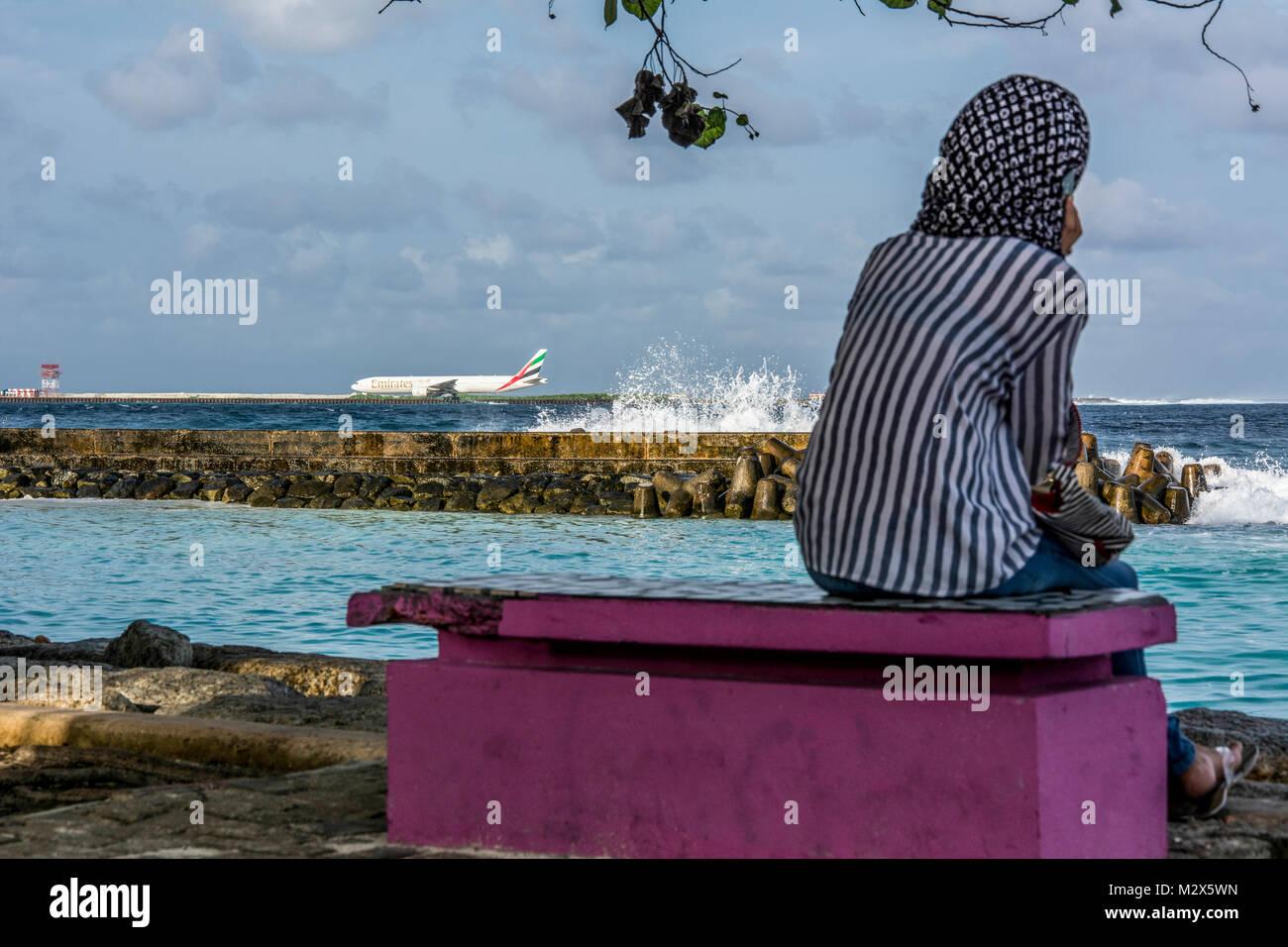 Muslimische Frau am Strand von Male mit Blick auf die Flughafeninsel Hulule mit landendem Flugzeug - Stock Image