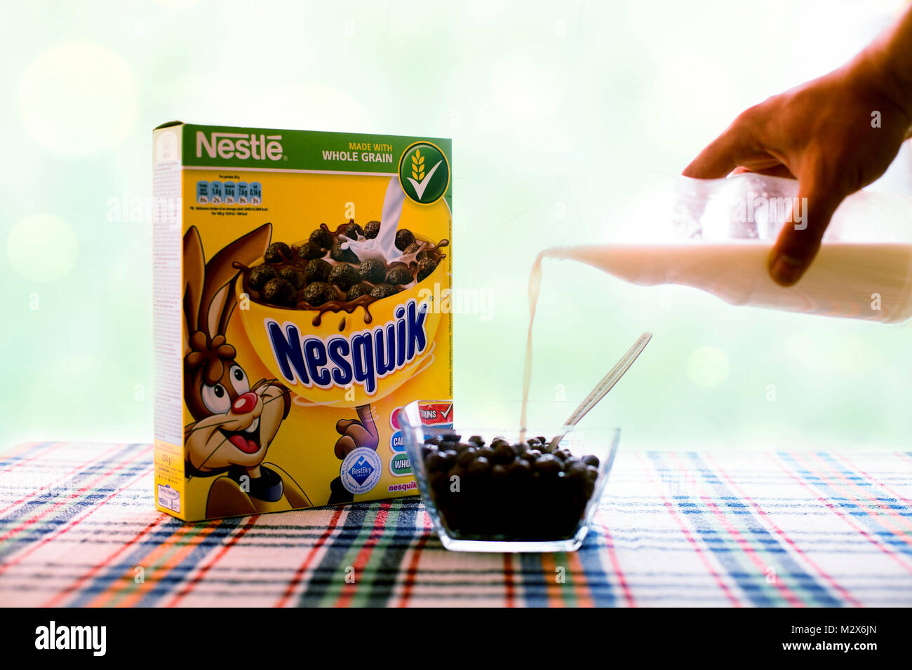 SOFIA , BULGAIRA  April 29, 2015: box Nesquick morning cereal and human hand with milk. Nesquick is made by Nestle - Stock Image