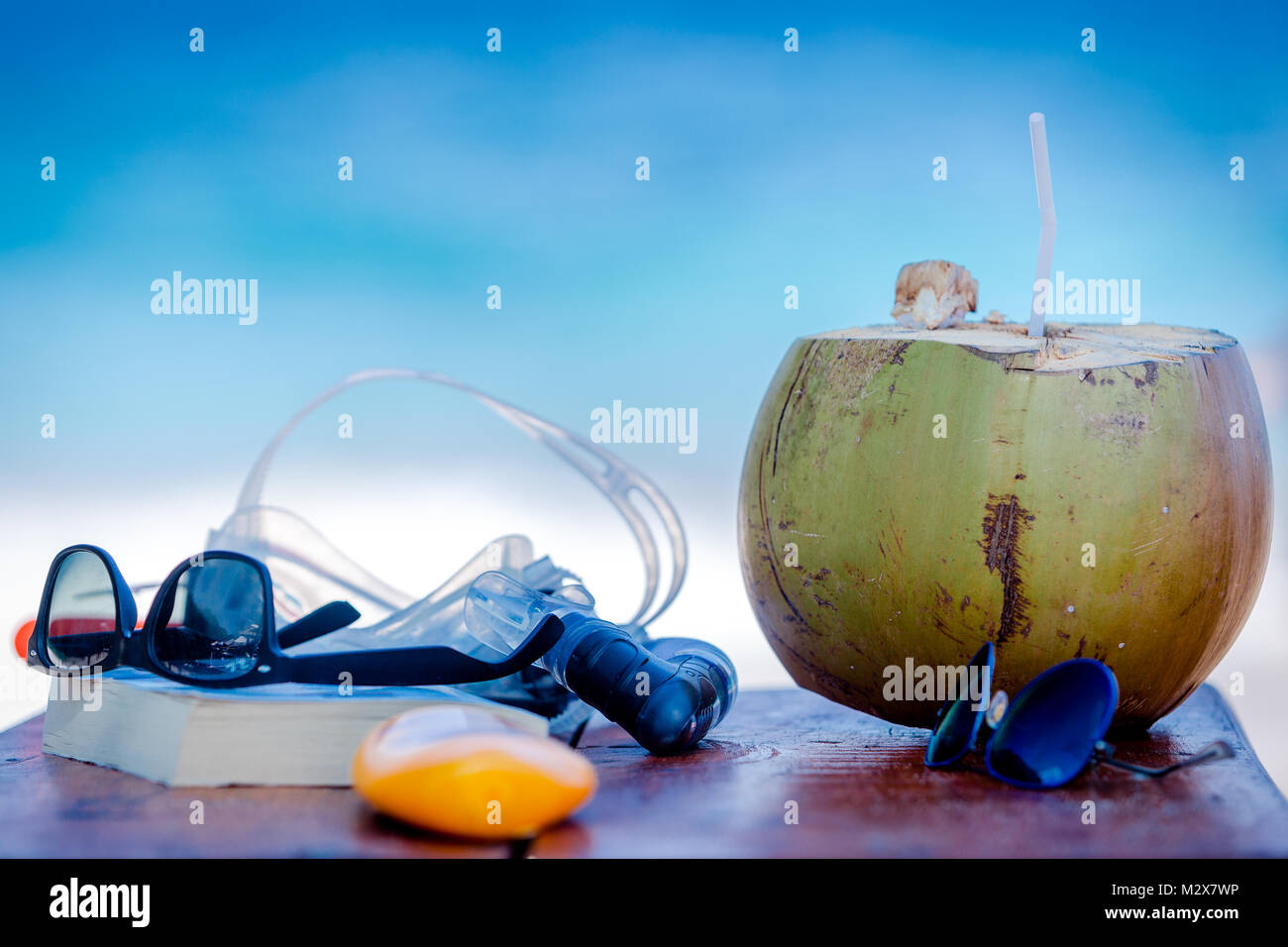 For rest on the beach attributes: book, sunglasses, tanning oil and fresh coconut water Stock Photo