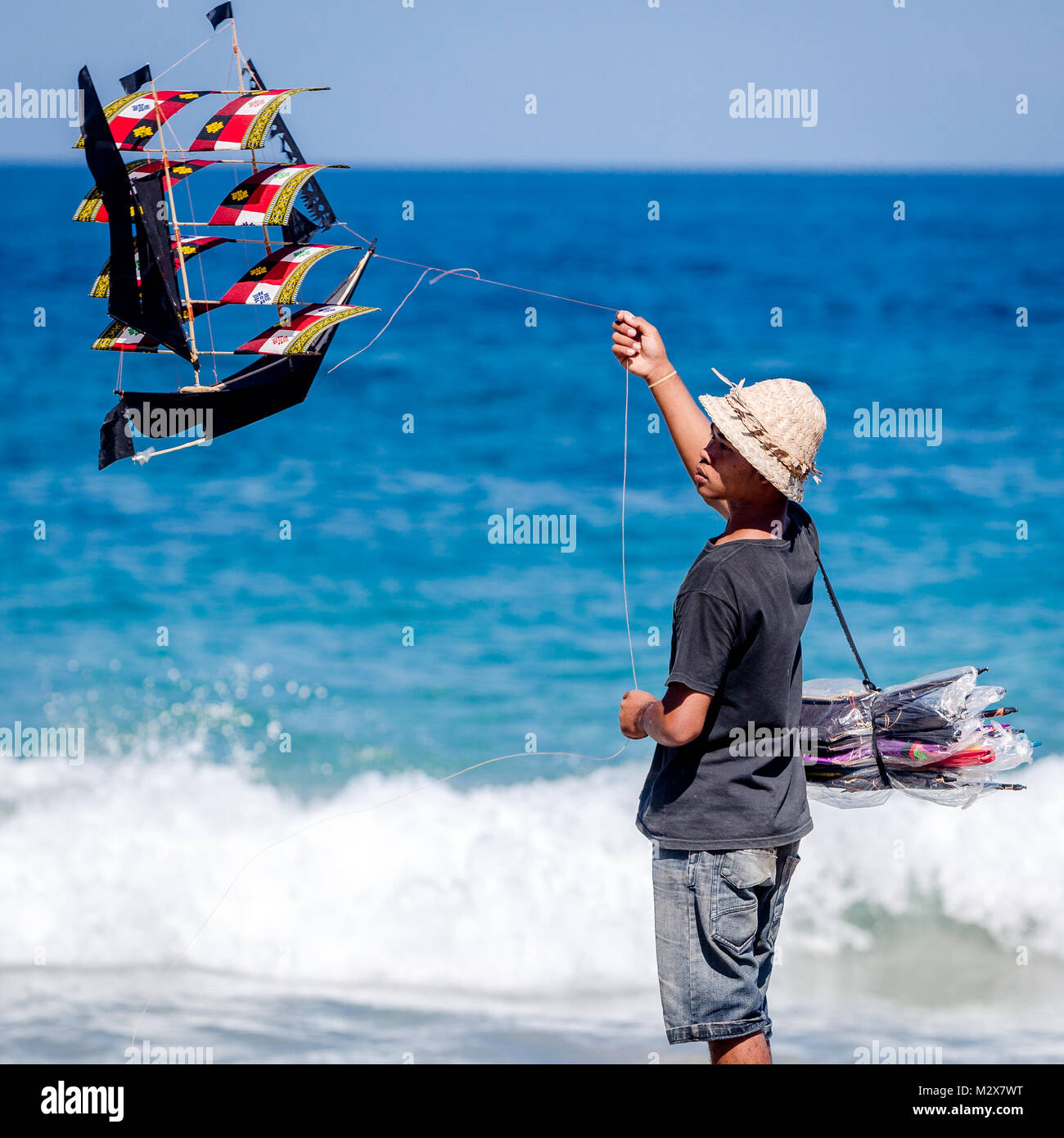 Bali, August 31, 2013: Balinese boy sells kites on the Bali beach Stock Photo