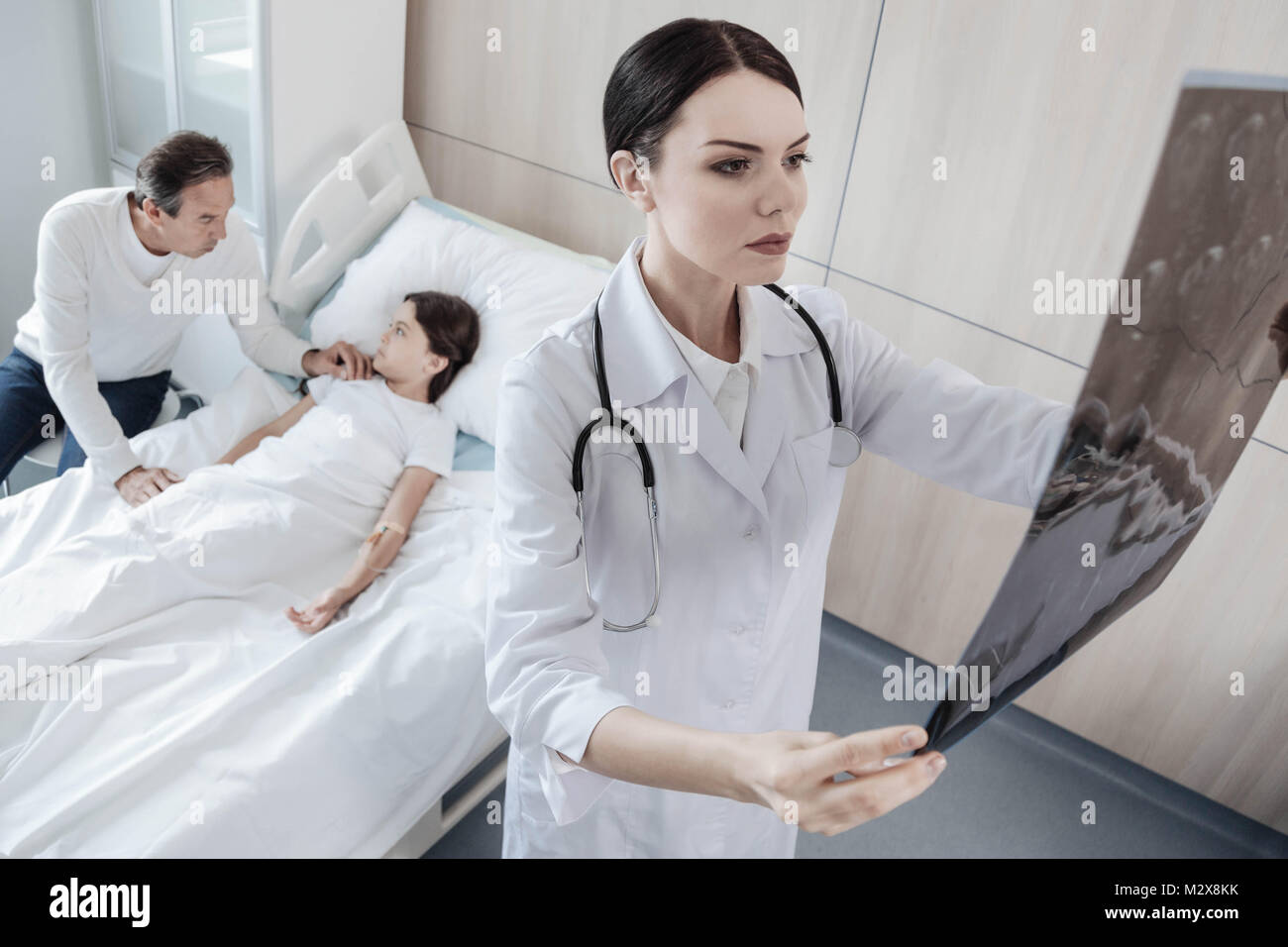 Serious physician examining computed tomography scans of little girl - Stock Image