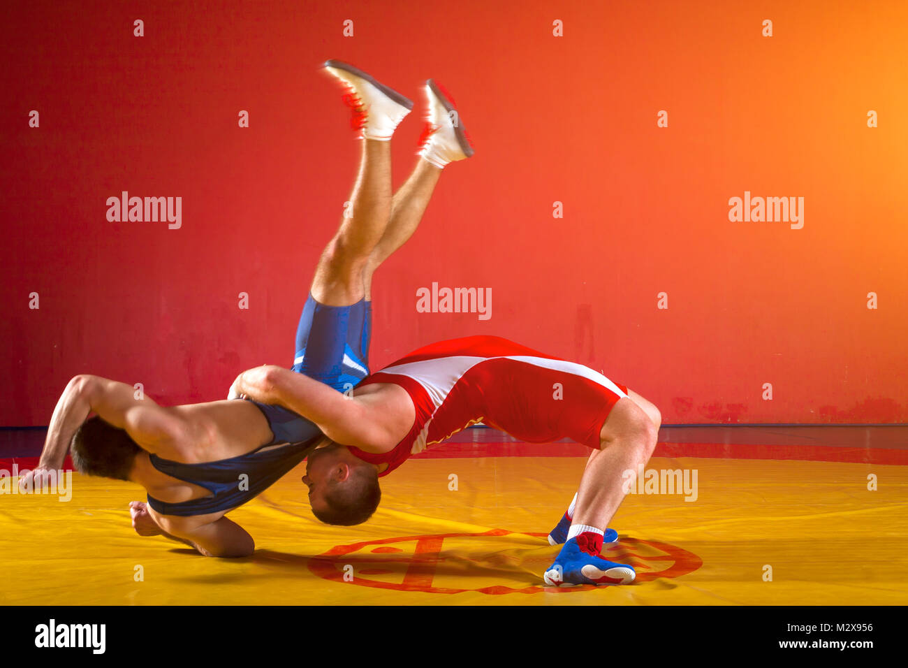 Two  strong men in blue and red wrestling tights are wrestlng and making a suplex wrestling on a yellow wrestling - Stock Image