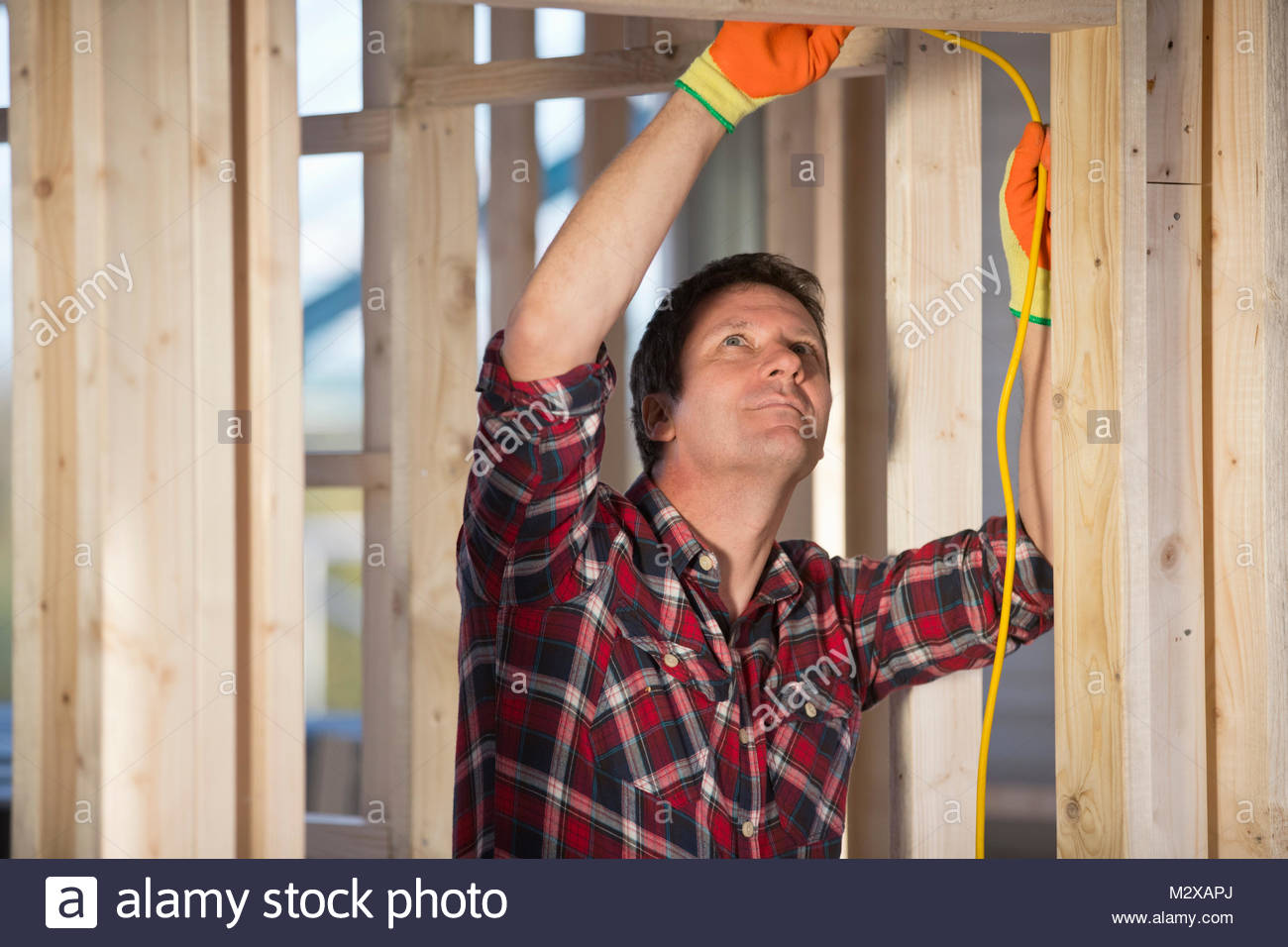 Electrician wiring room on indoor building construction site Stock ...