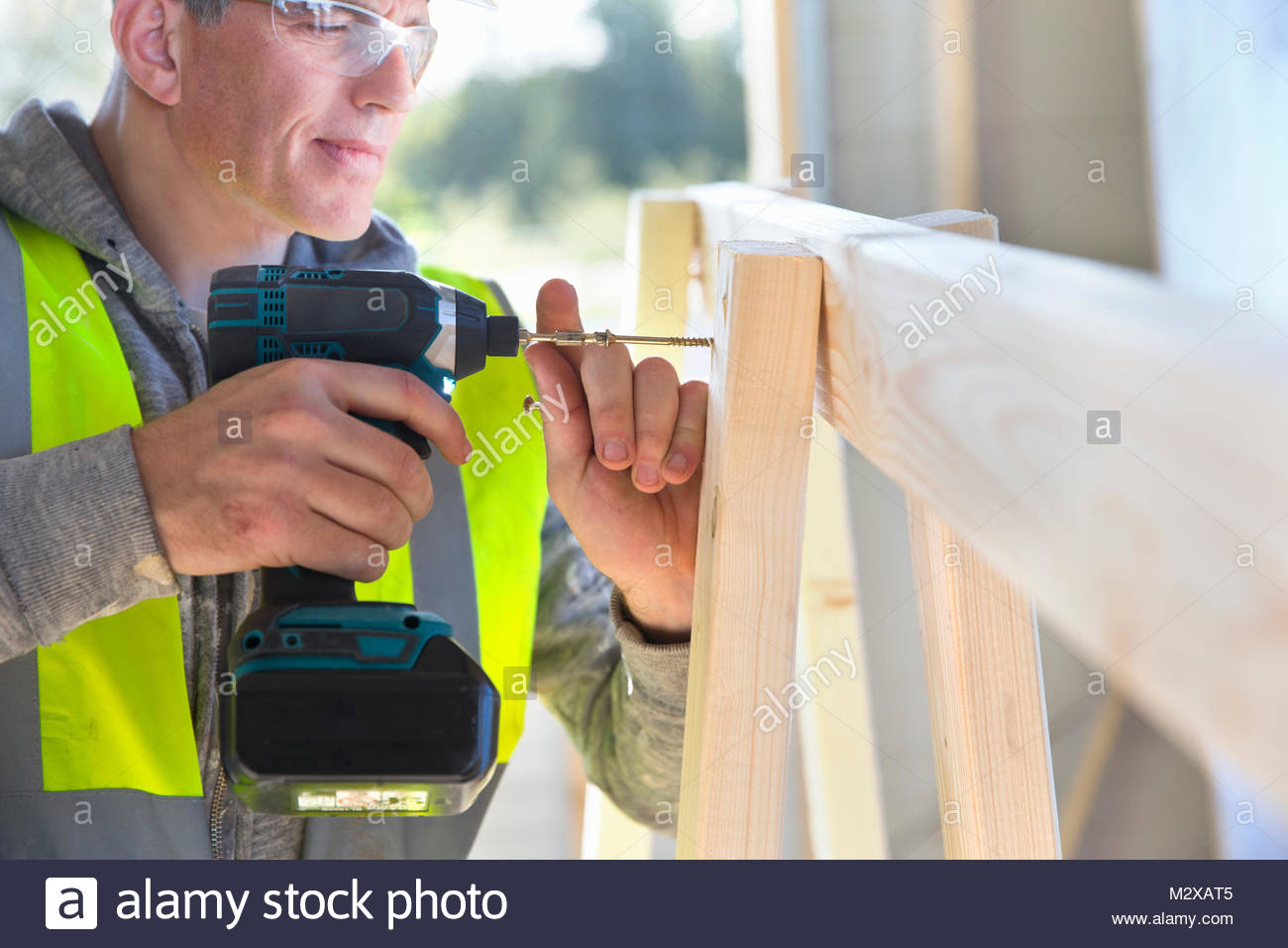Carpenter using power drill to screw wood frame together on construction site interior - Stock Image