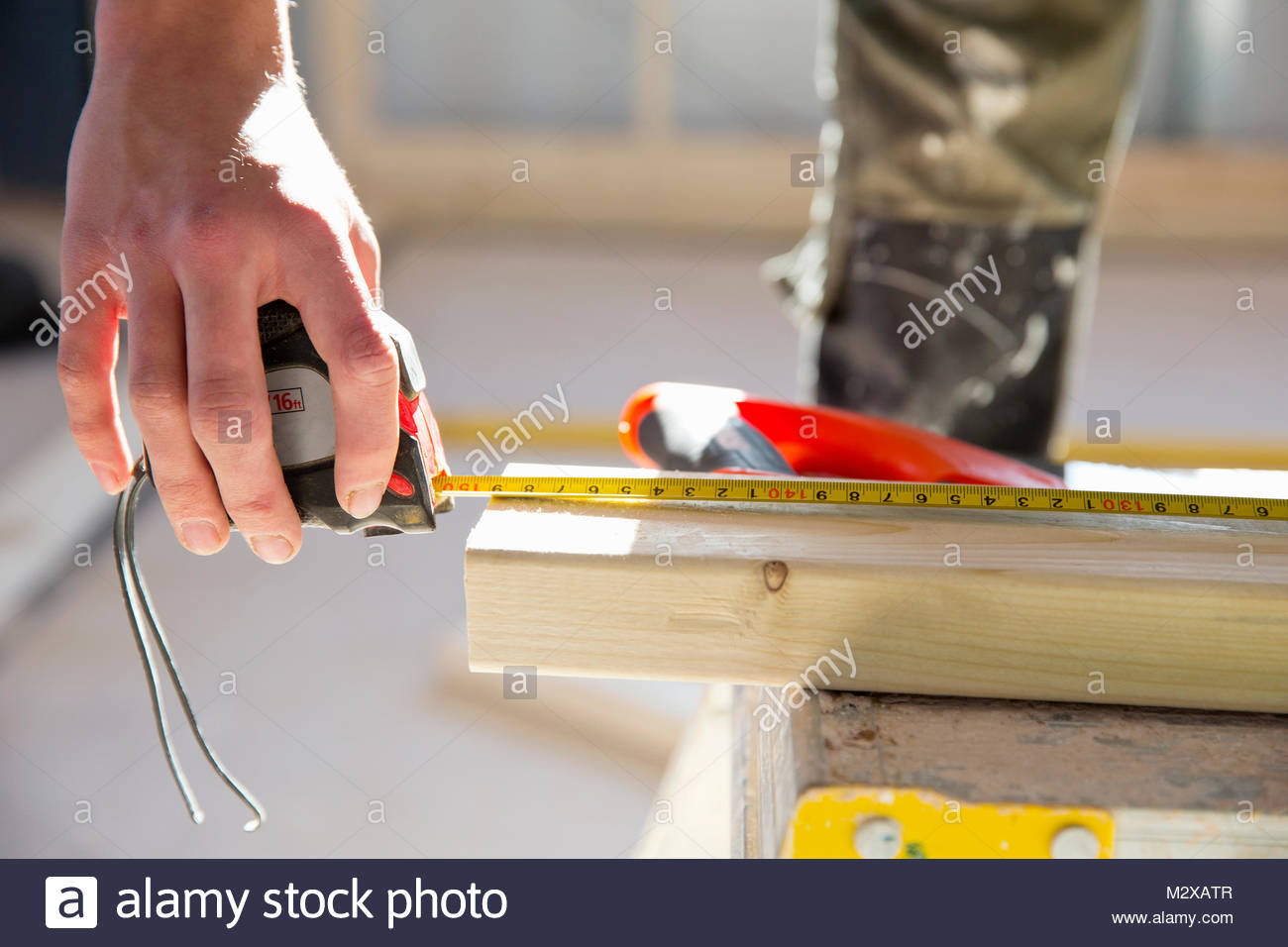 Close-up of carpenter measuring piece of wood on construction site interior - Stock Image