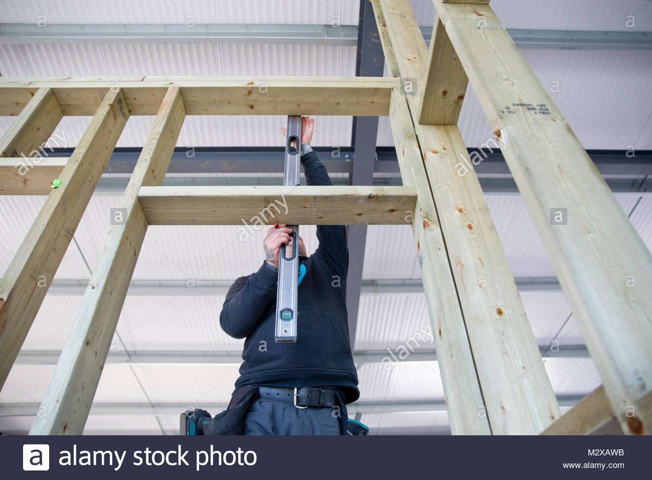 Carpenter using spirit level to check angle of wood frame on construction site interior - Stock Image
