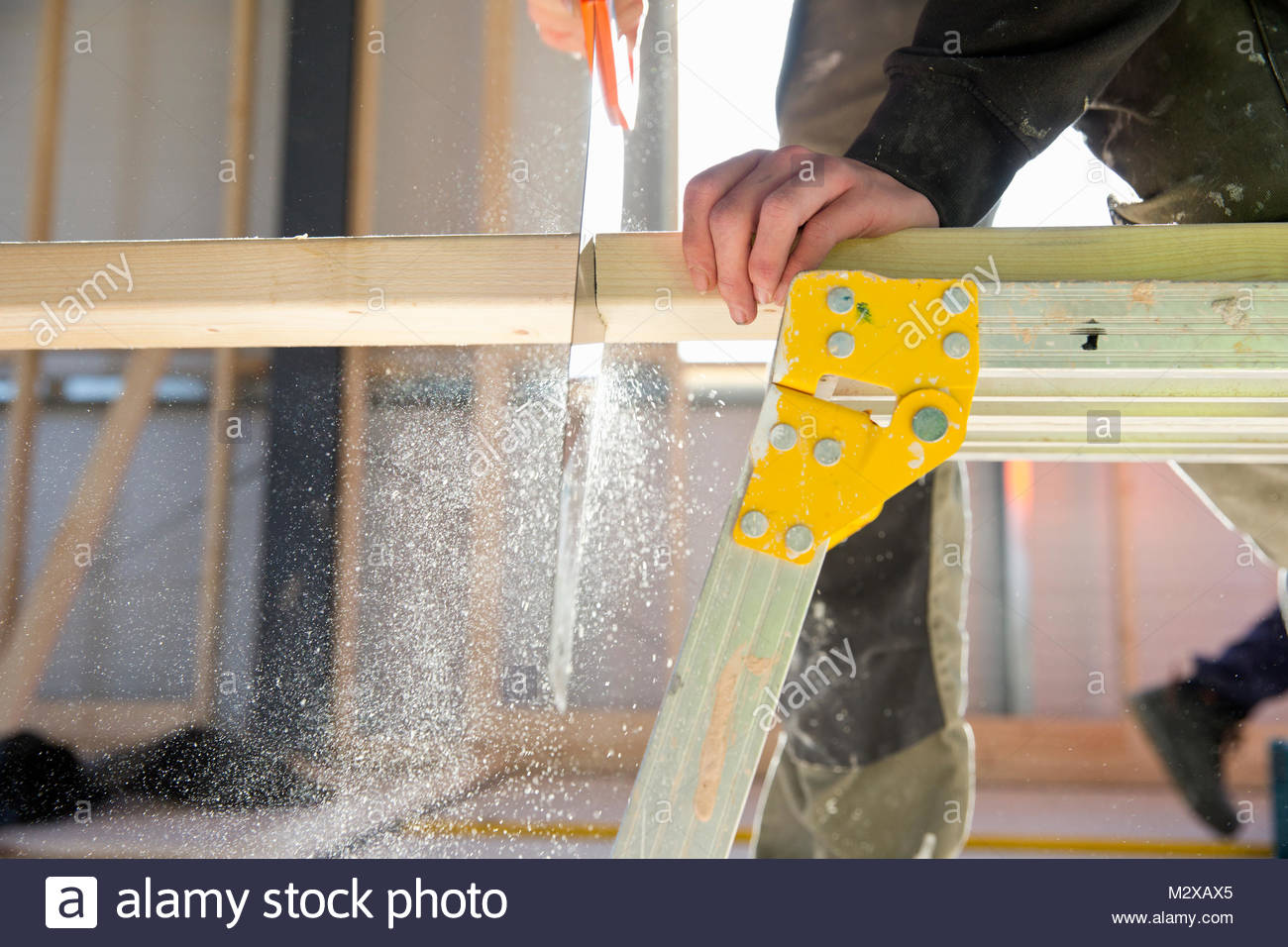 Close-up of carpenter sawing piece of wood on construction site interior - Stock Image