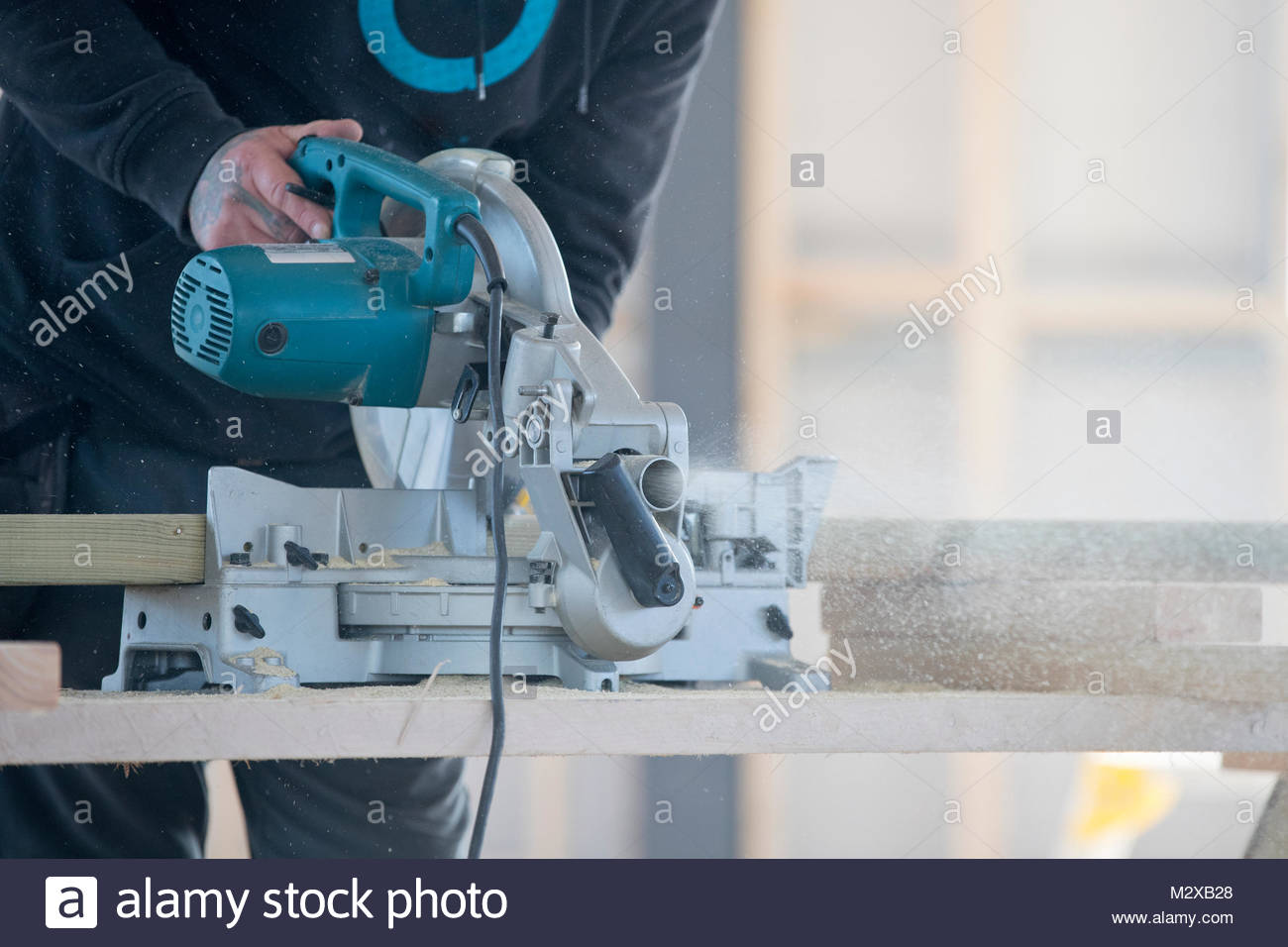 Carpenter using circular power saw tool to cut wood in construction site interior - Stock Image