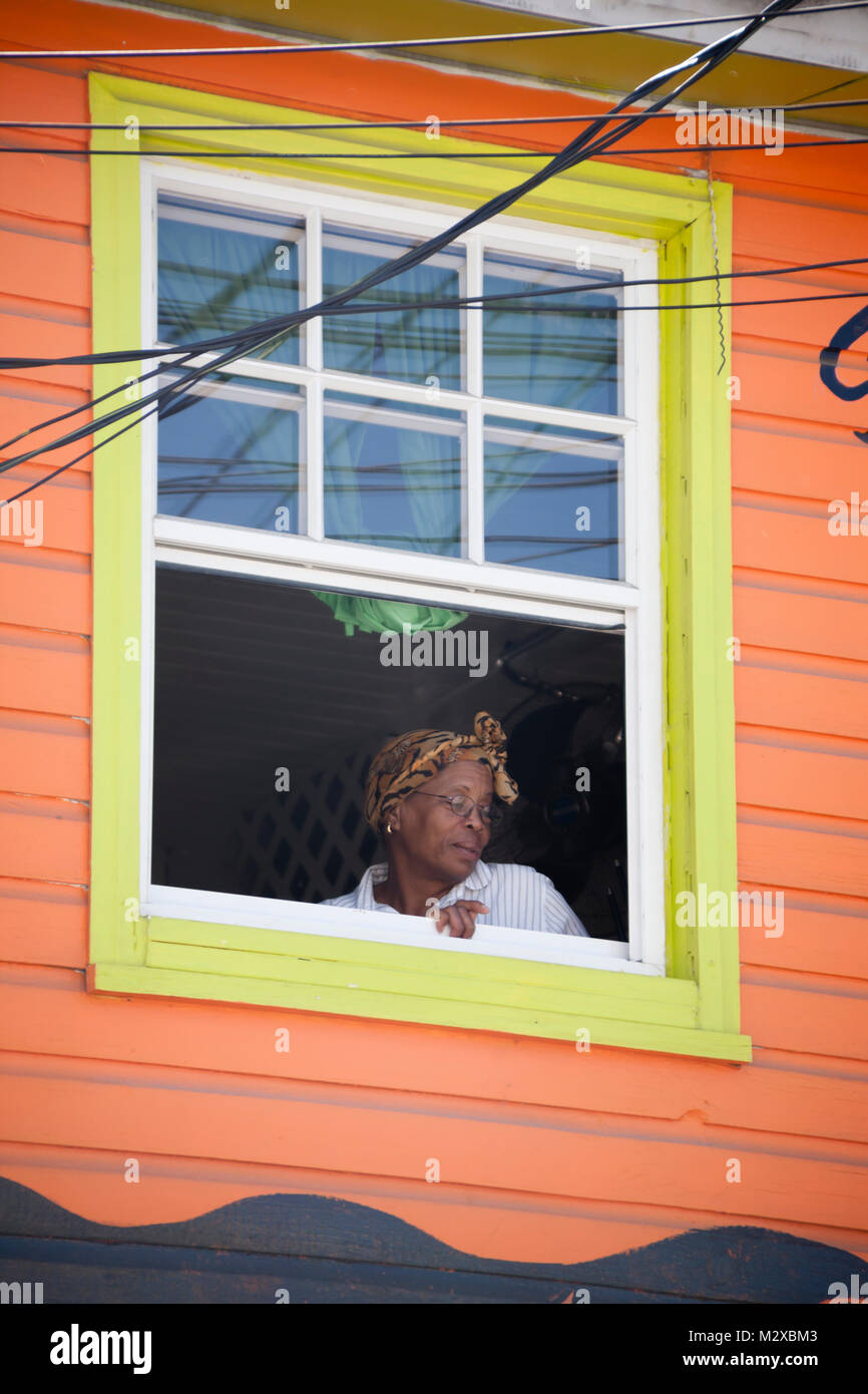 Close up of an Afro Caribbean women sat looking out of an old wooden house window frame on the Caribbean Island - Stock Image
