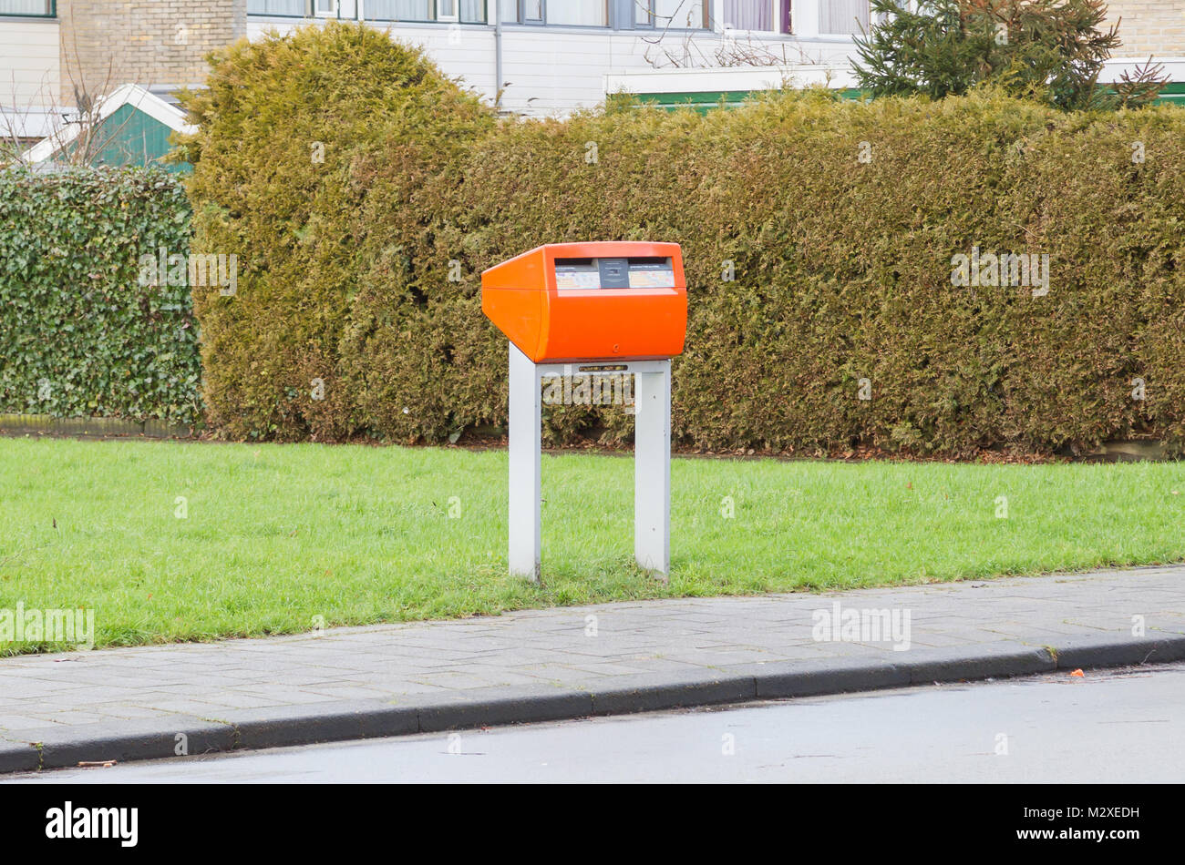 Posting a letter in the Netherlands - Orange letterbox Stock Photo