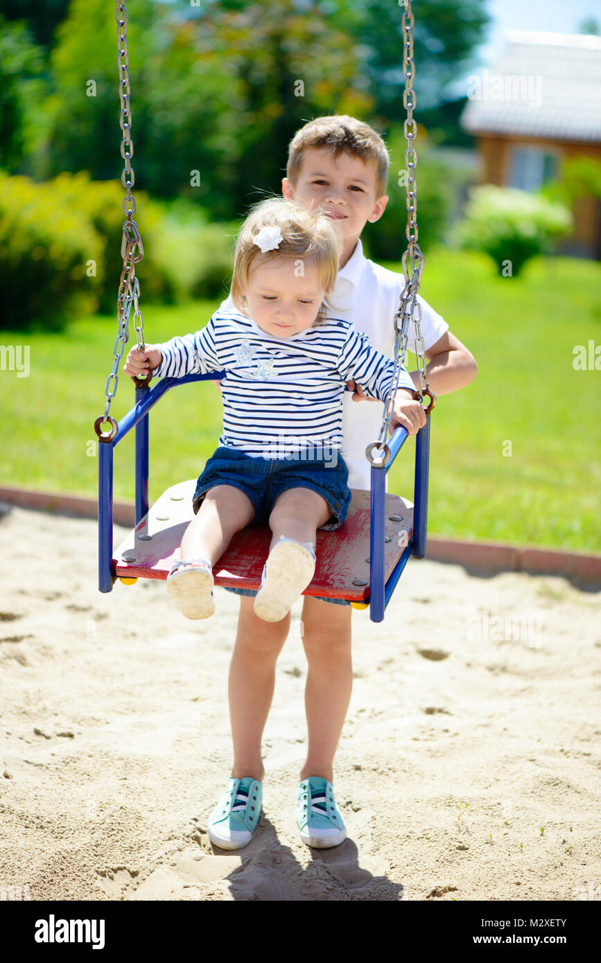 b753c3f571aa9 Little cute brother and sister swinging in summer park Stock Photo ...