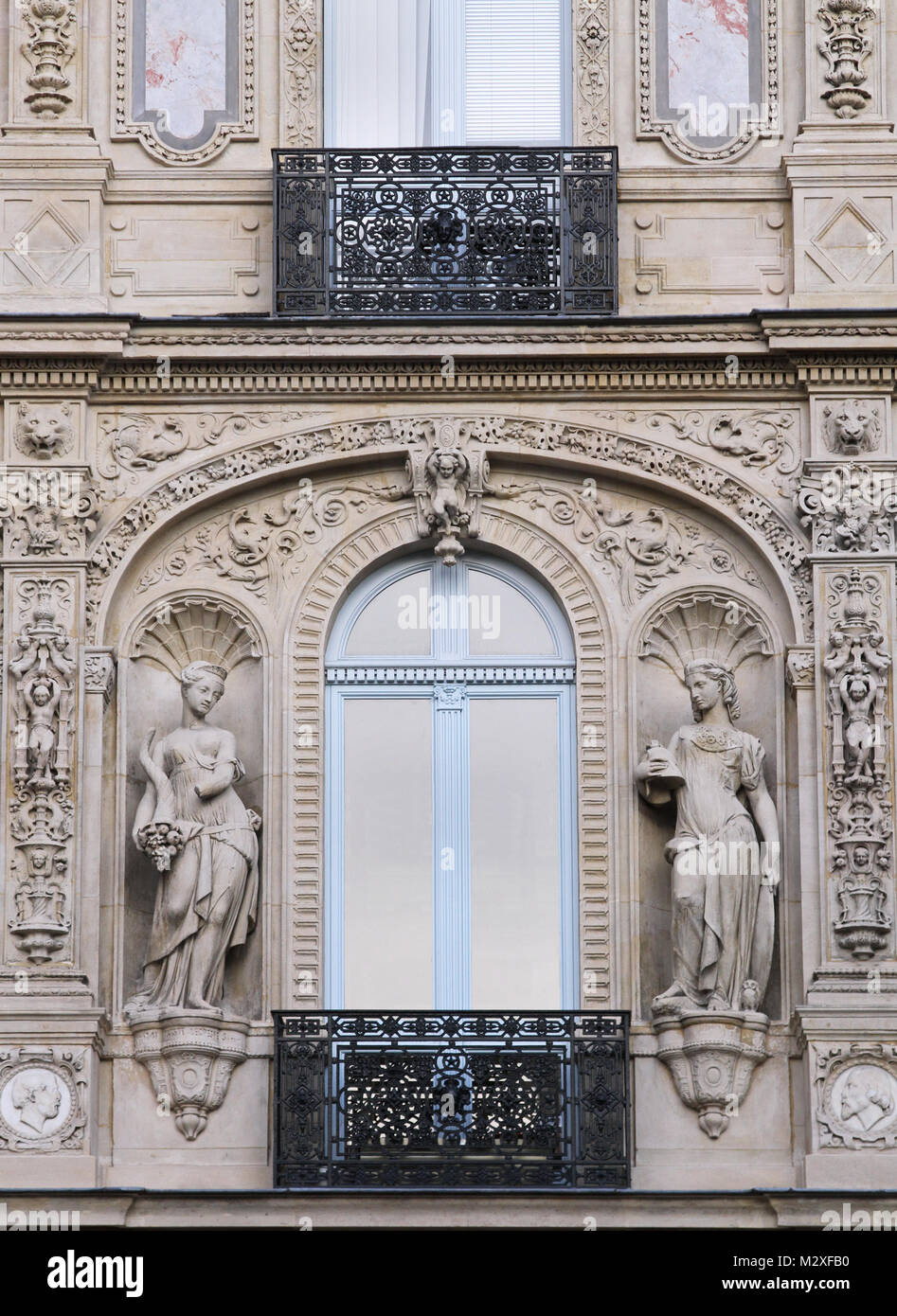 Old Paris architecture building facade with stone statues - Stock Image