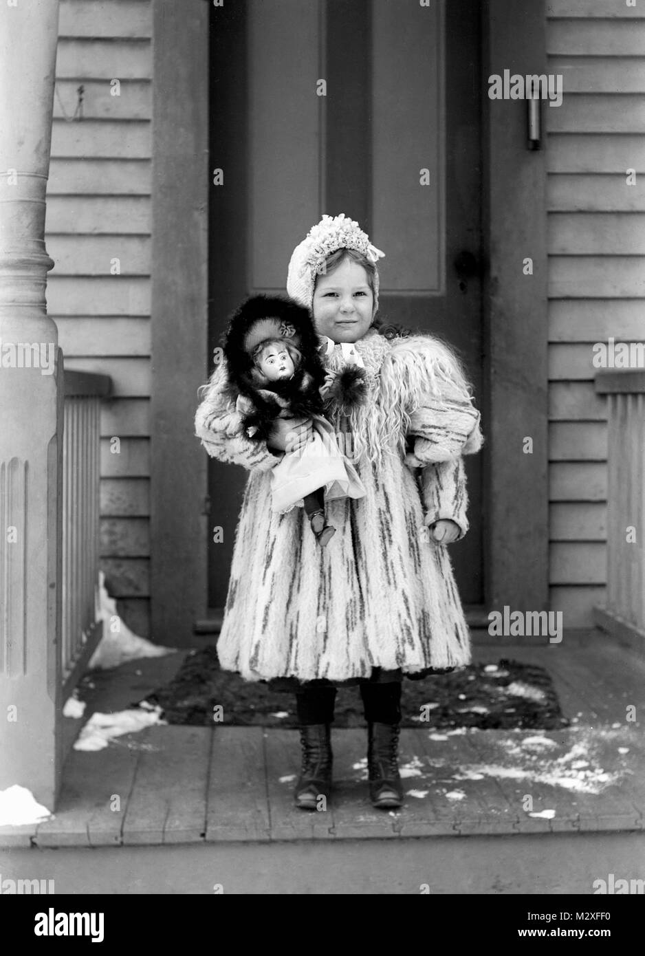 Young well-dressed girl holds her doll on the front porch, ca. 1910. - Stock Image