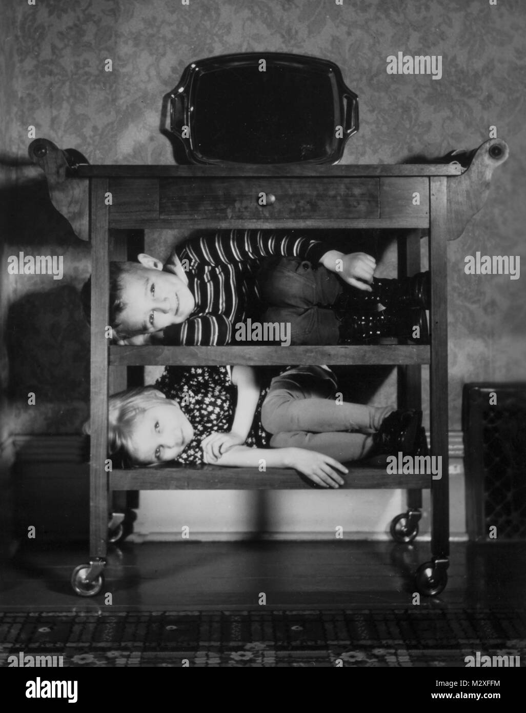 Brother and sister are stacked on a period tea cart, ca. 1938. - Stock Image
