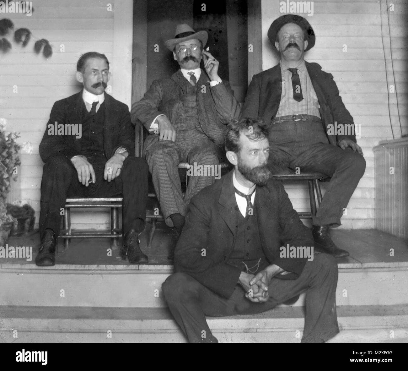 Four men sit on the porch, ca. 1910. - Stock Image