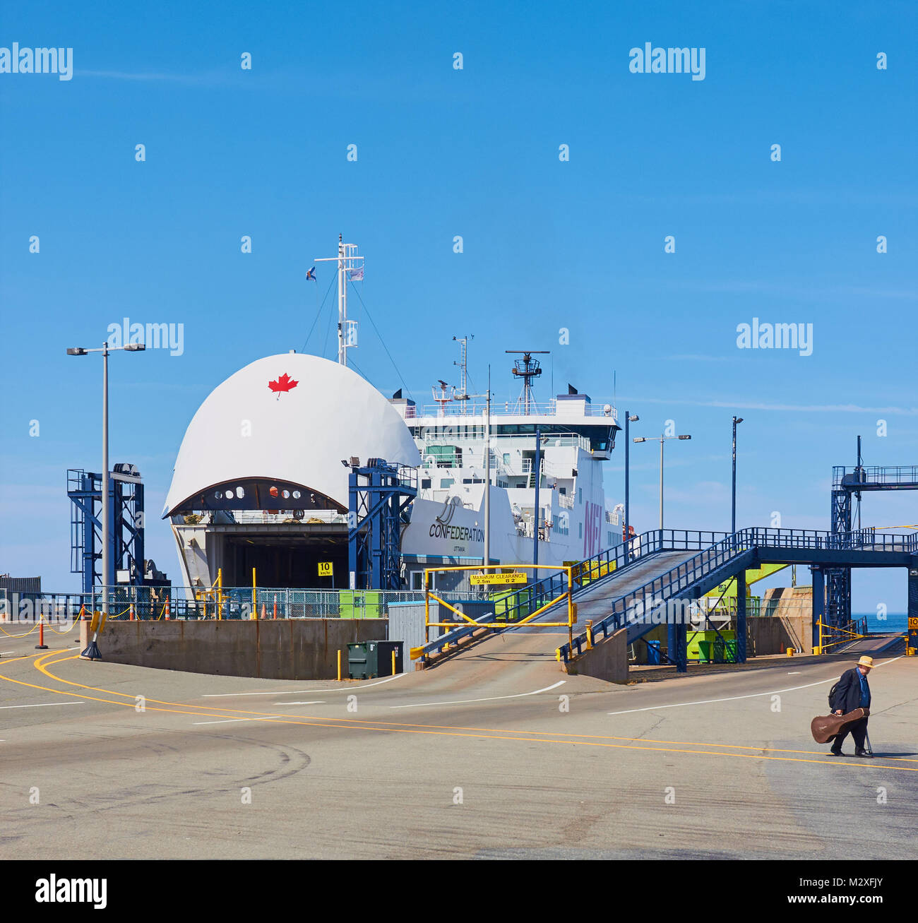 Foot passenger disembarking from a Northumberland ferry carrying a guitar case, Caribou, Nova Scotia, Canada. Stock Photo