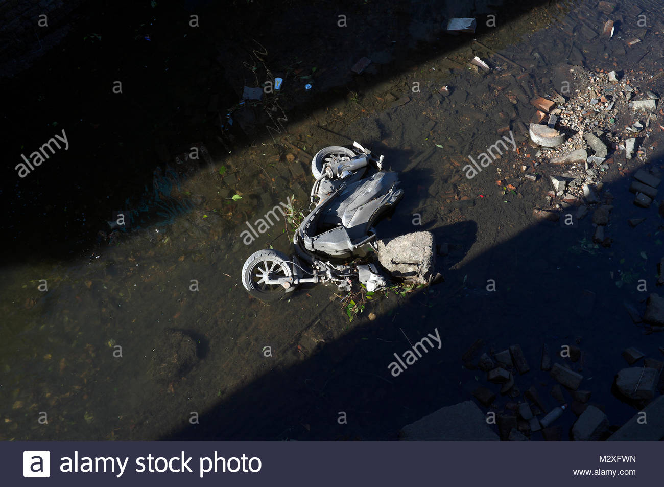 A dumped scooter in a drained section of the Grand Union Canal in Birmingham, West Midlands, UK. - Stock Image
