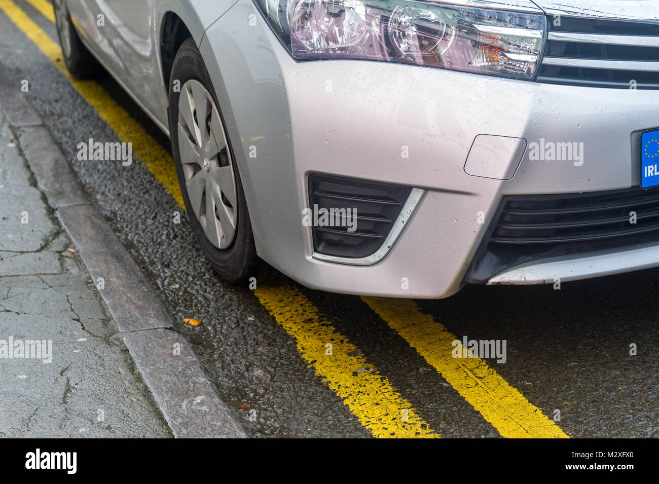 Car parked on double yellow lines/parking violation in Skibbereen, County Cork, Ireland - Stock Image