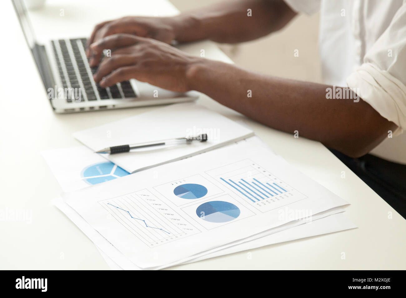 Data analysis and business statistics concept, african-american businessman using laptop analyzing work result infographic - Stock Image