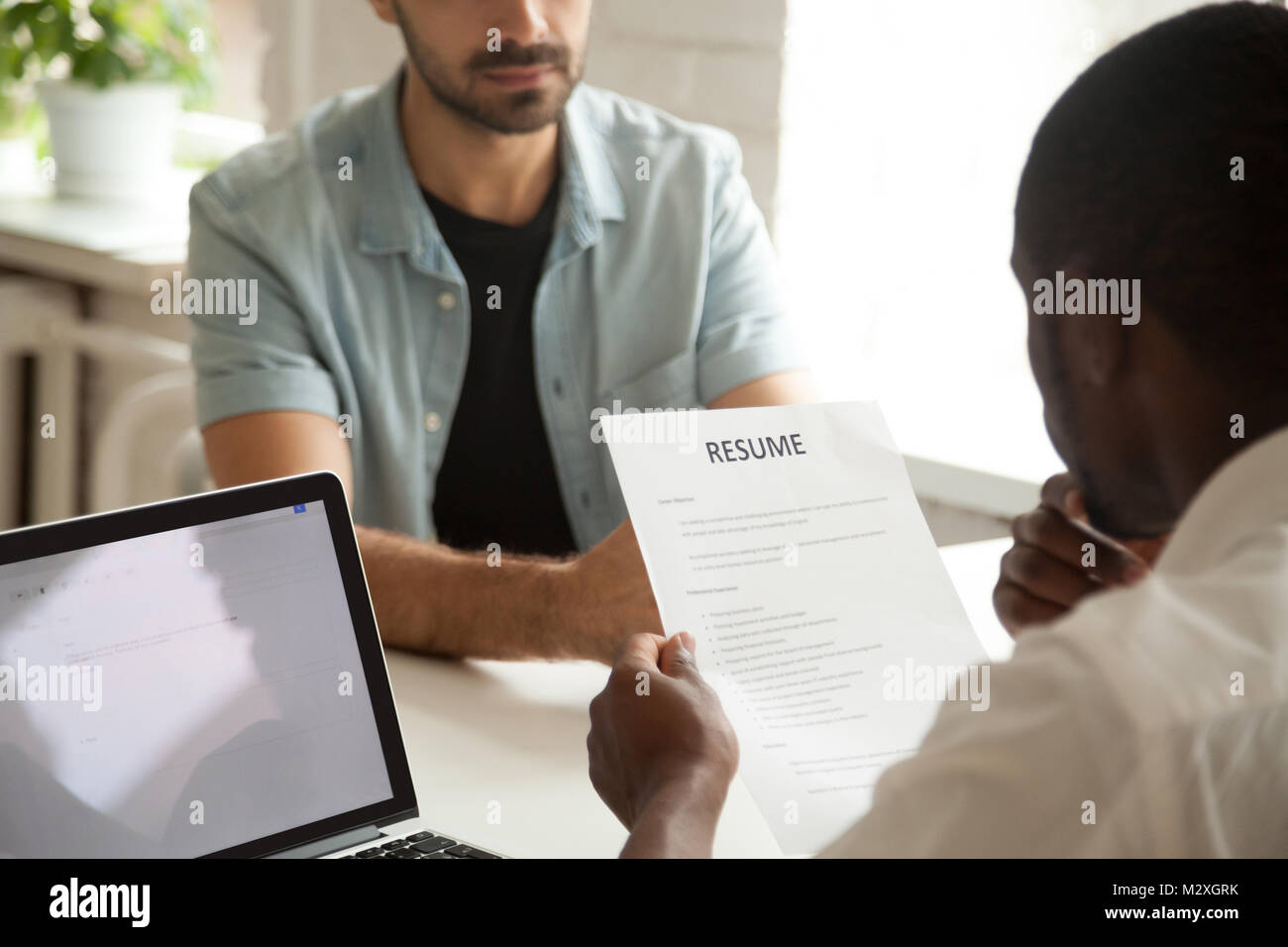 African american hr manager holding applicants curriculum vitae at job interview, black recruiter or employer considering - Stock Image