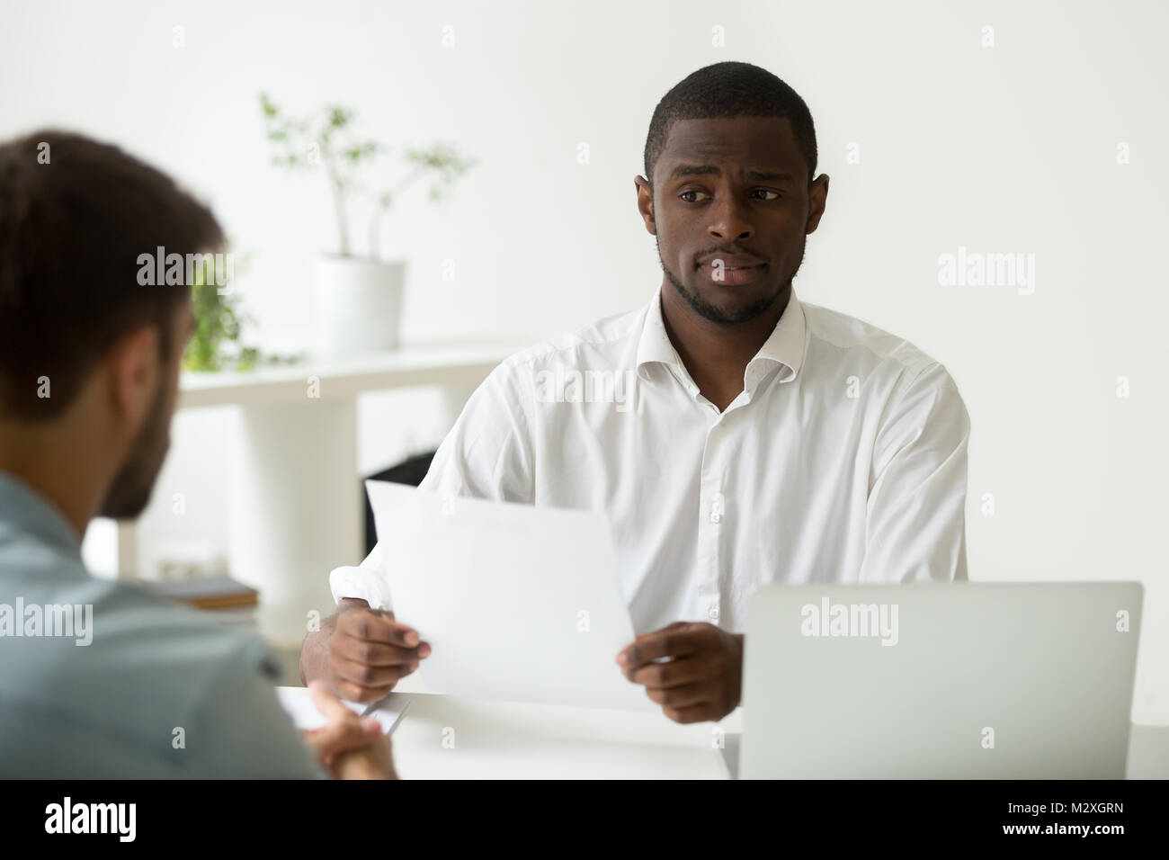 African american hr manager looking doubtful about hiring incompetent candidate, uncertain distrustful black employer - Stock Image