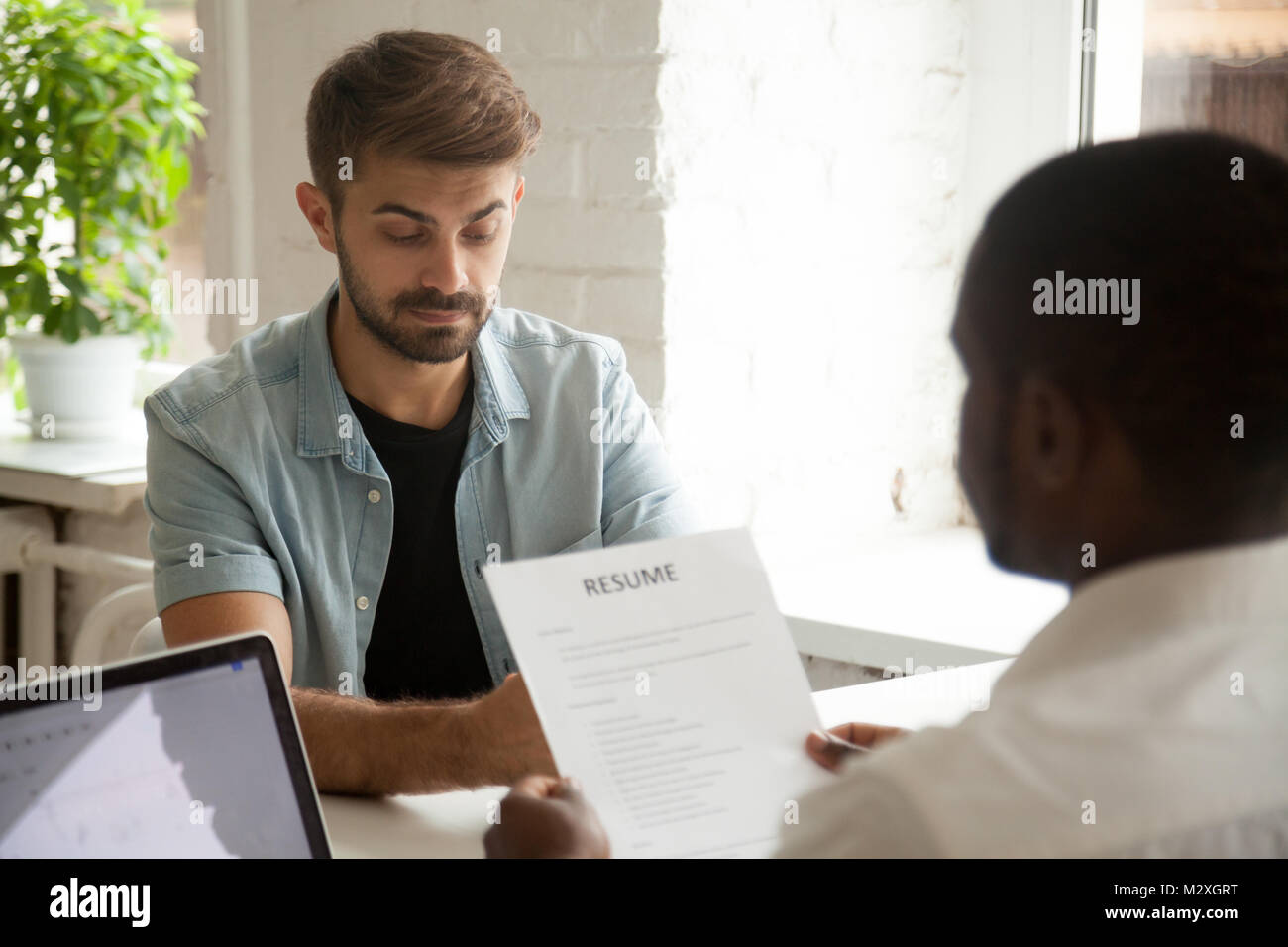 Stressed caucasian applicant feels worried while african hr employer reading resume, stress at job interview concept, - Stock Image