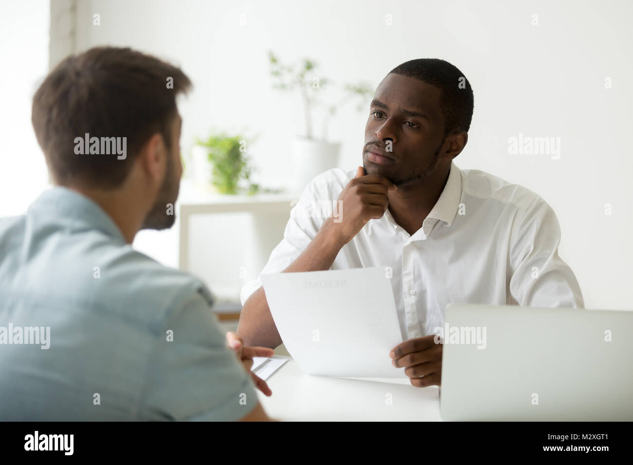 Serious attentive african hr manager listening to caucasian candidate at job interview, focused strict employer - Stock Image