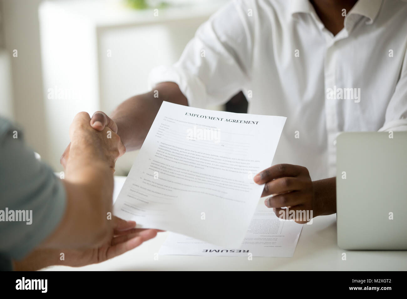African american employer holding employment agreement offering new job welcoming successful vacancy candidate, - Stock Image