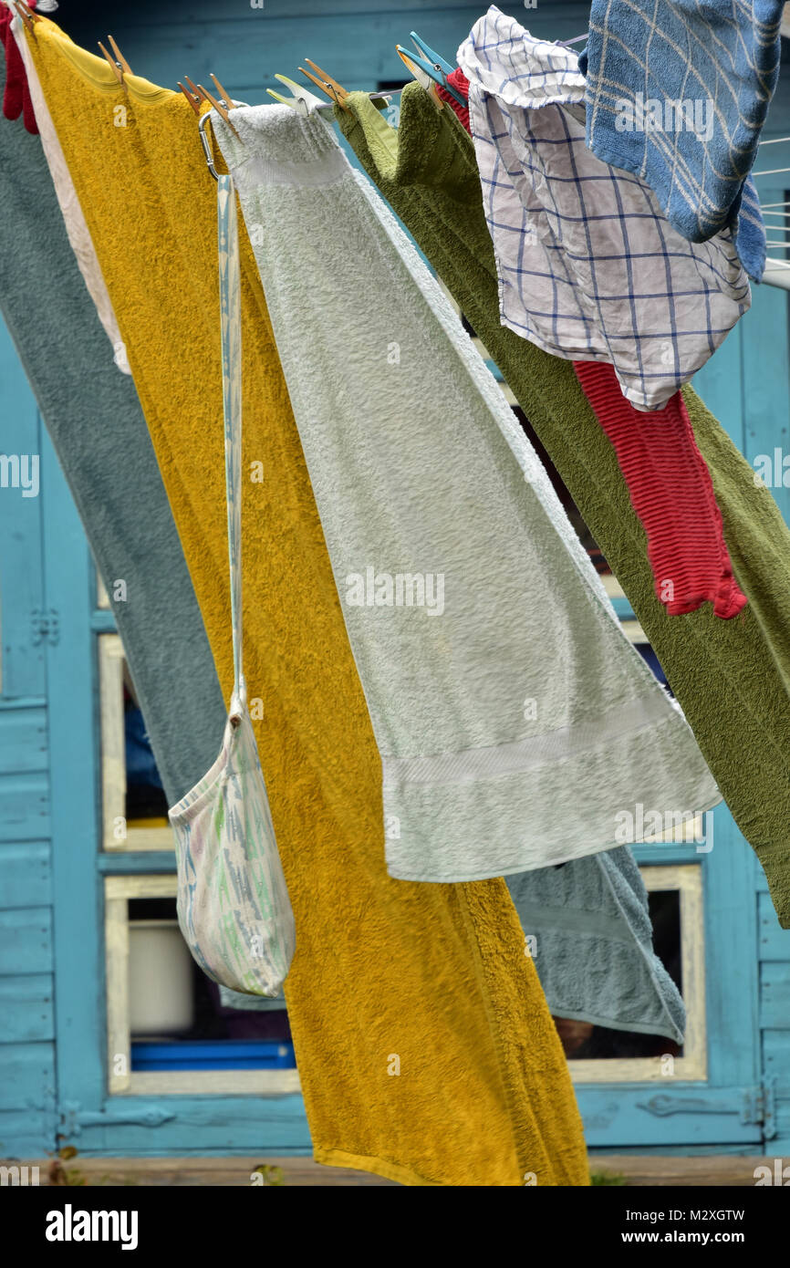 tea towels and bath towels hanging out on a washing line held with pegs and blowing laundry in the wind. washing - Stock Image