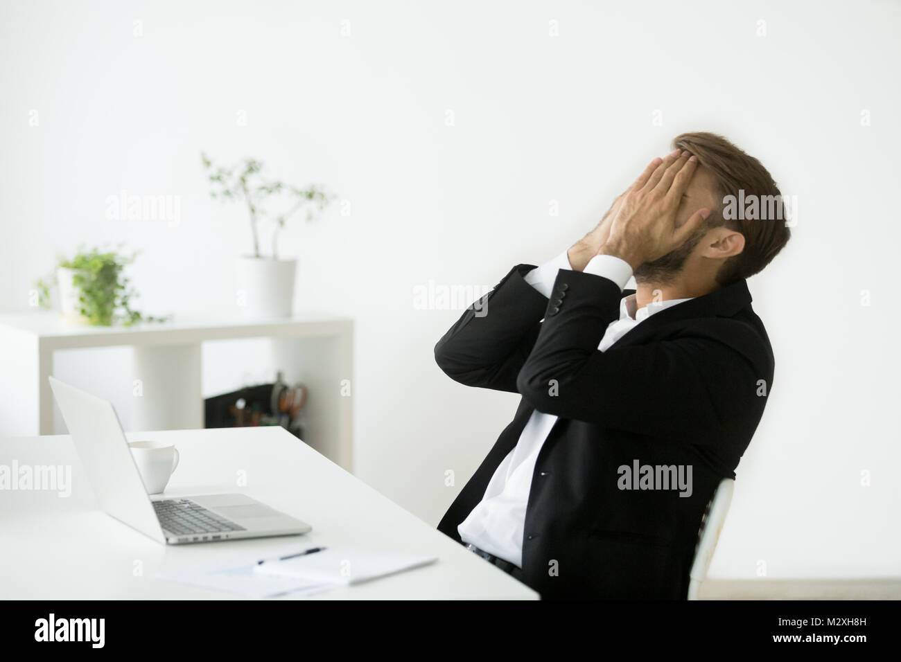 Distraught stressed bankrupt businessman covering face with hand - Stock Image