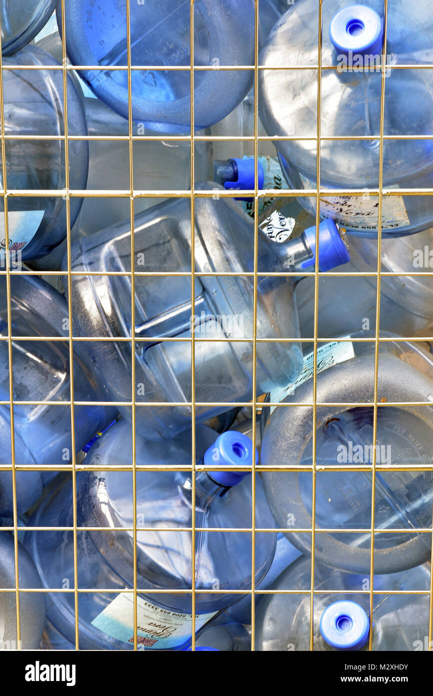 Large plastic water bottles being collected and delivered to a business premises in metal cages. Plastics damaging - Stock Image