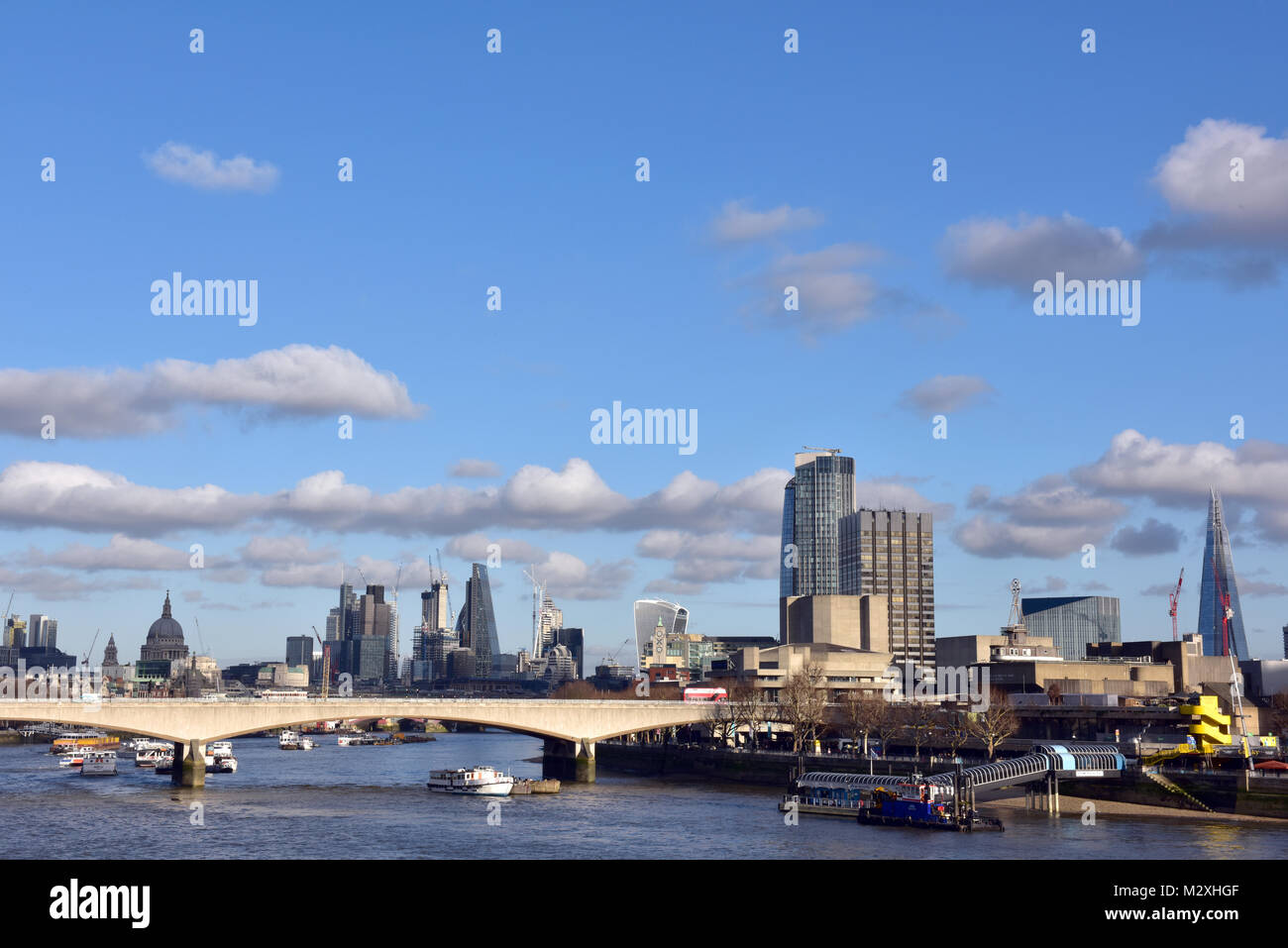 The London city skyline on a clear winters day with blue sky and clouds. Iconic buildings and architecture including - Stock Image