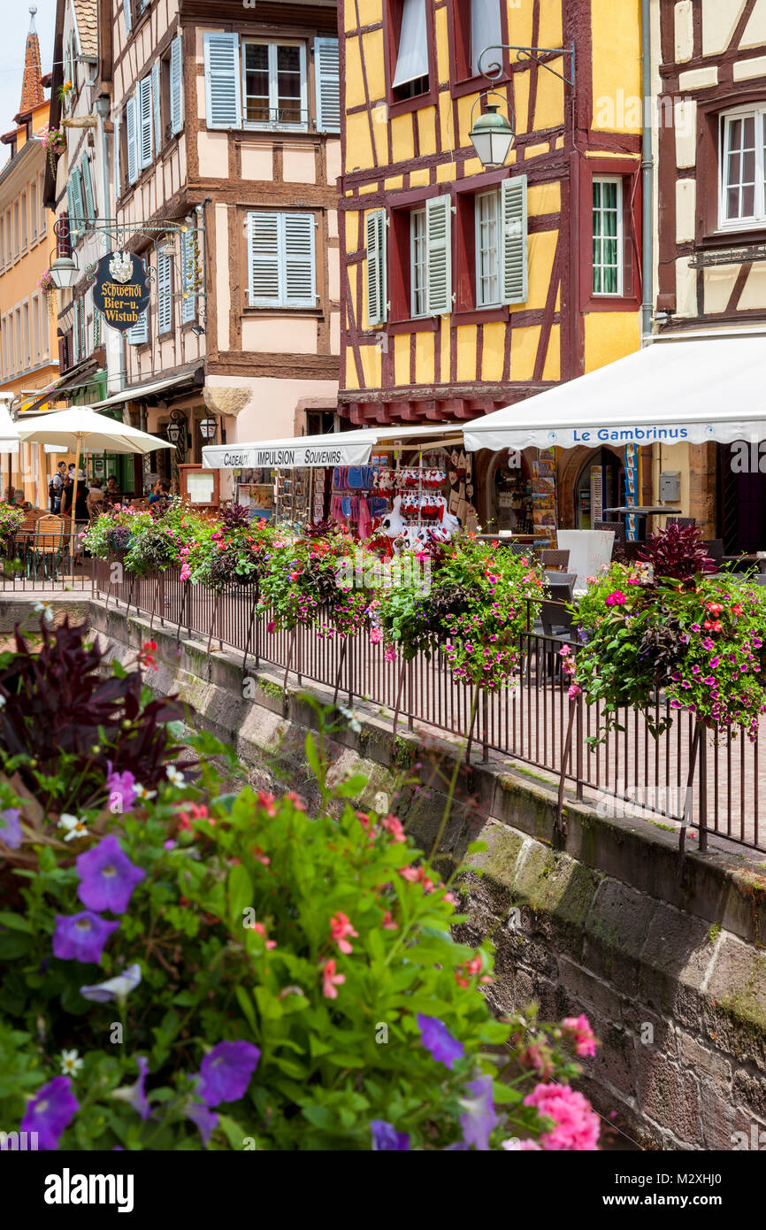 Half-timbered buildings, flowers and street scene in old Colmar, Alsace, France - Stock Image