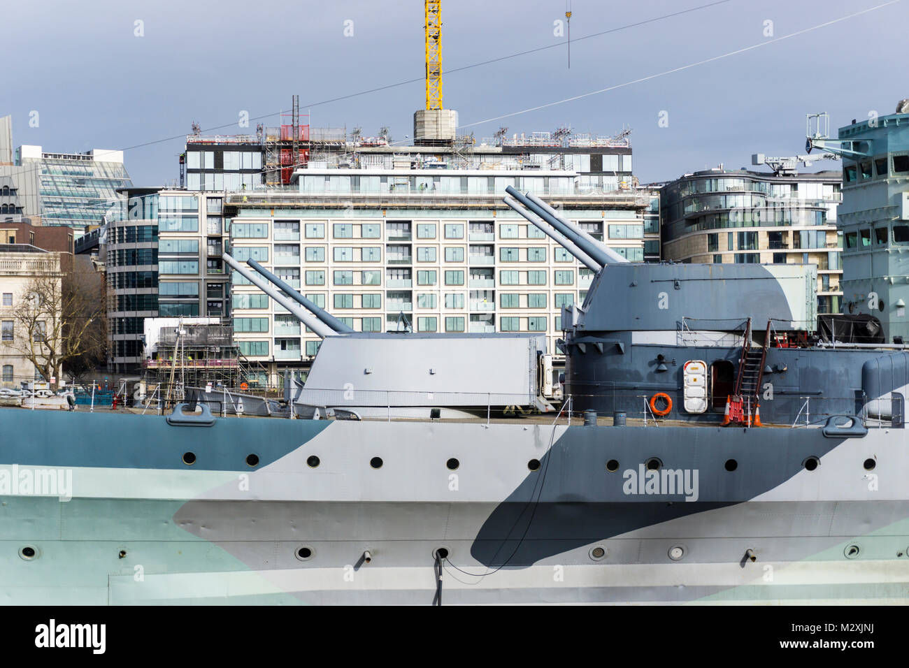 The forward guns of HMS Belfast are famously trained on the Scratchwood Services, now London Gateway service station, - Stock Image