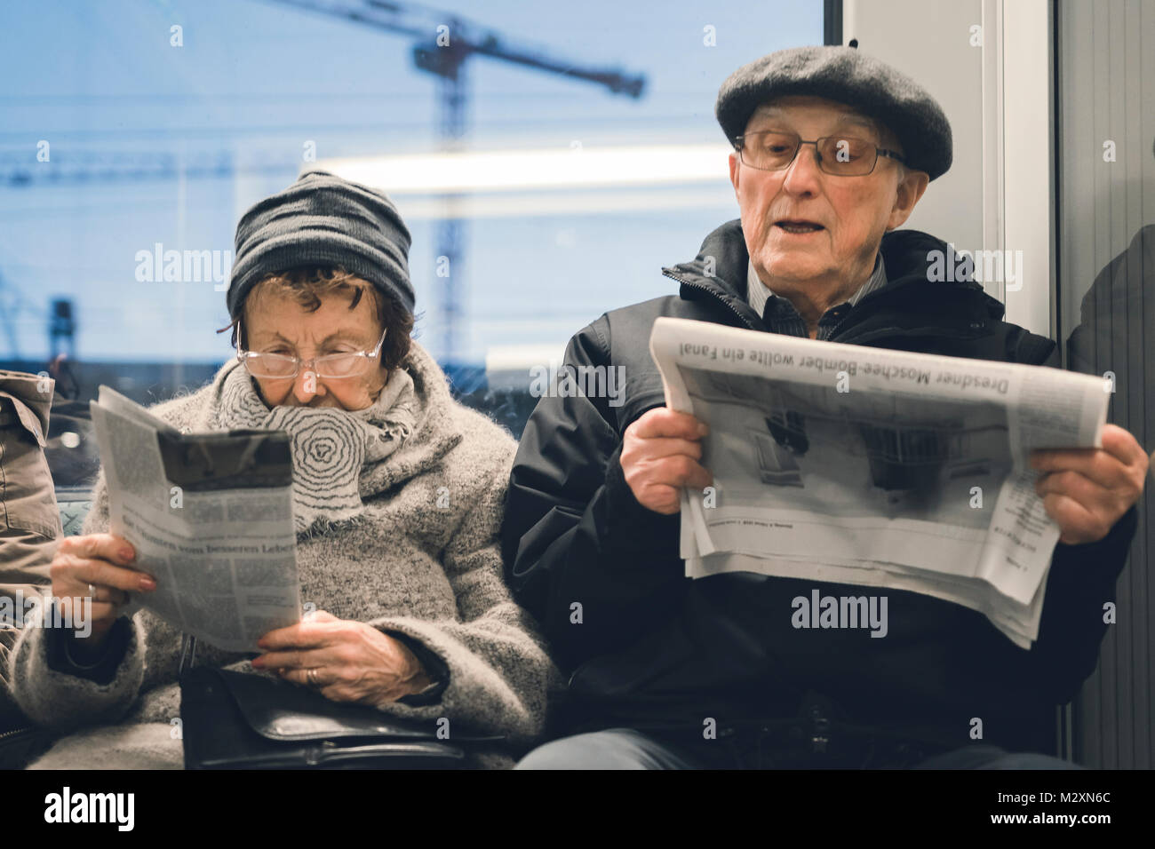 Elderly couple reading the newspaper on the S-Bahn, Berlin. - Stock Image