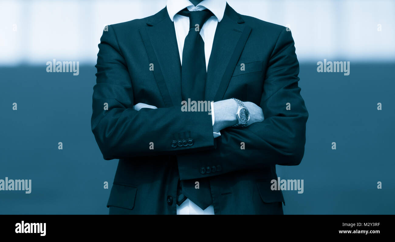 Success business man with arms crossed. Blue Toned Image. Stock Photo
