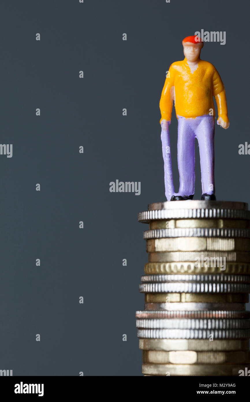 Pension concept. Old person figure on a stack of coins - Stock Image