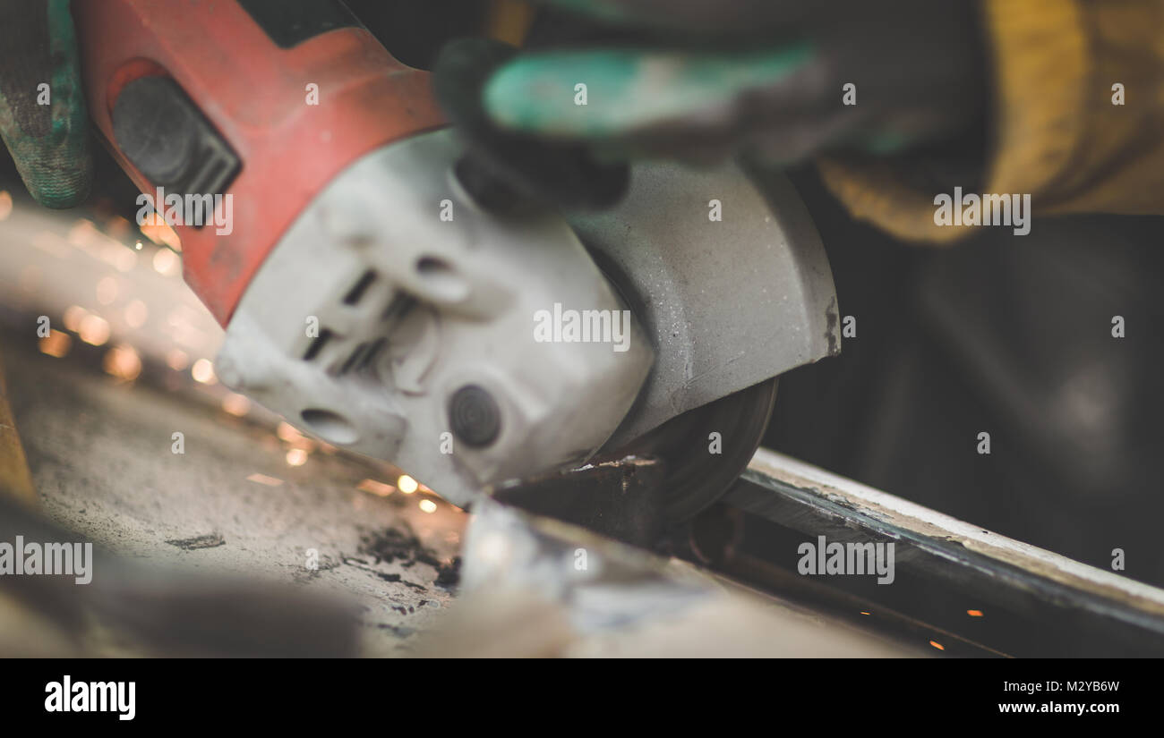 Craftsman sawing metal with disk angle grinder in a warehouse. - Stock Image