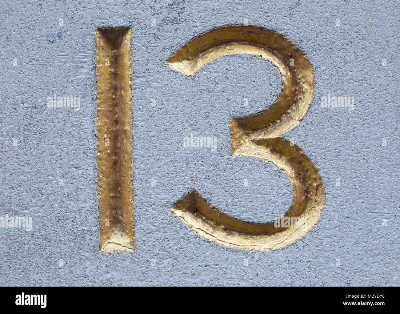 Number 13 in bevelled gold gilded numerals chased into light stone. - Stock Image