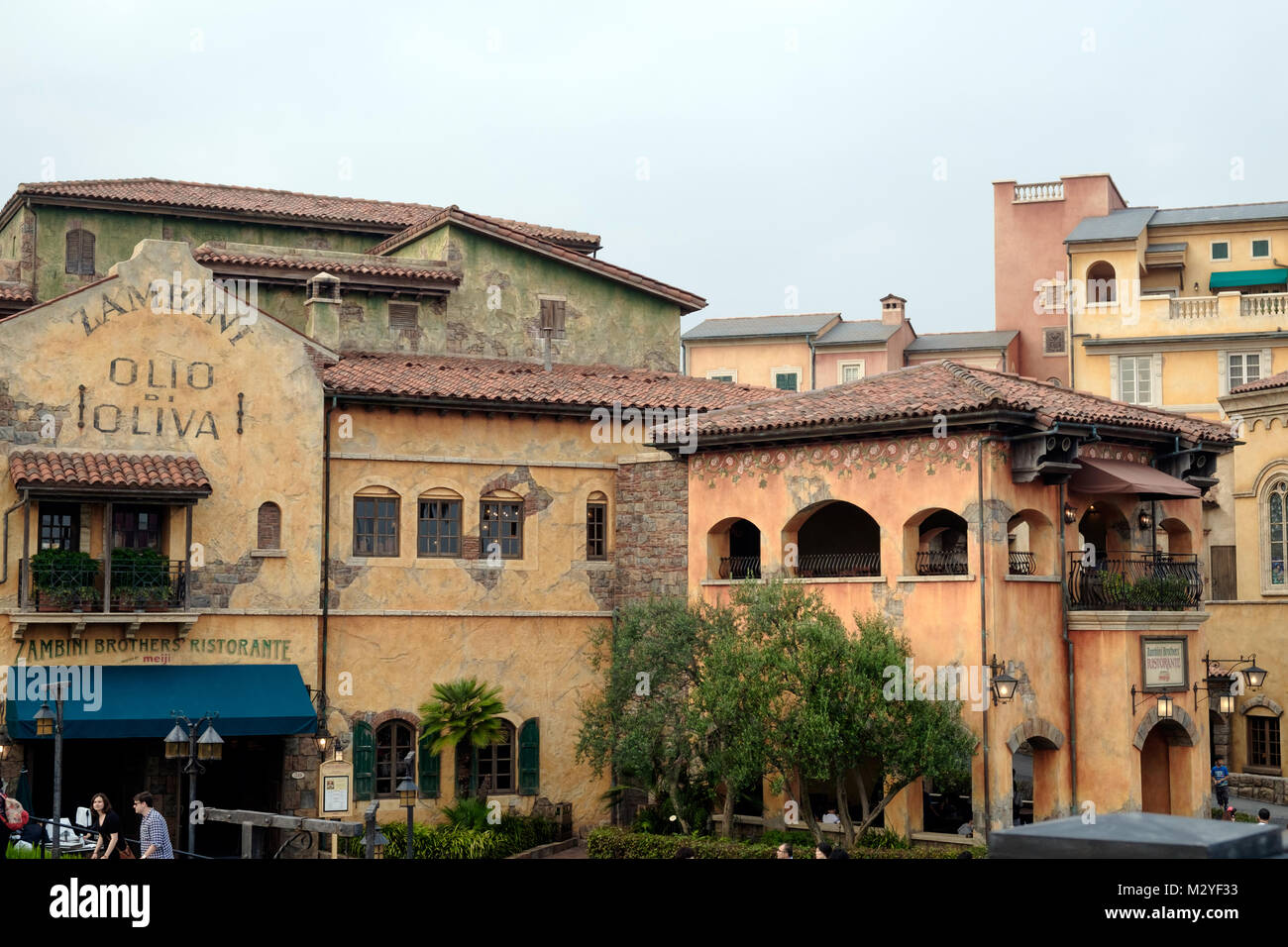 Tuscany Italy style architecture. Weathered old pale orange buildings with terracotta tiled roofs. Restaurant with - Stock Image