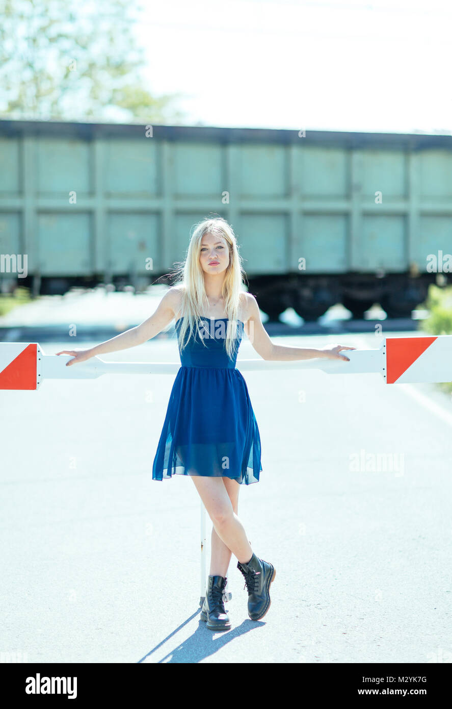 Young blonde woman waiting on automated level crossing with down barriers for oncoming train - Stock Image