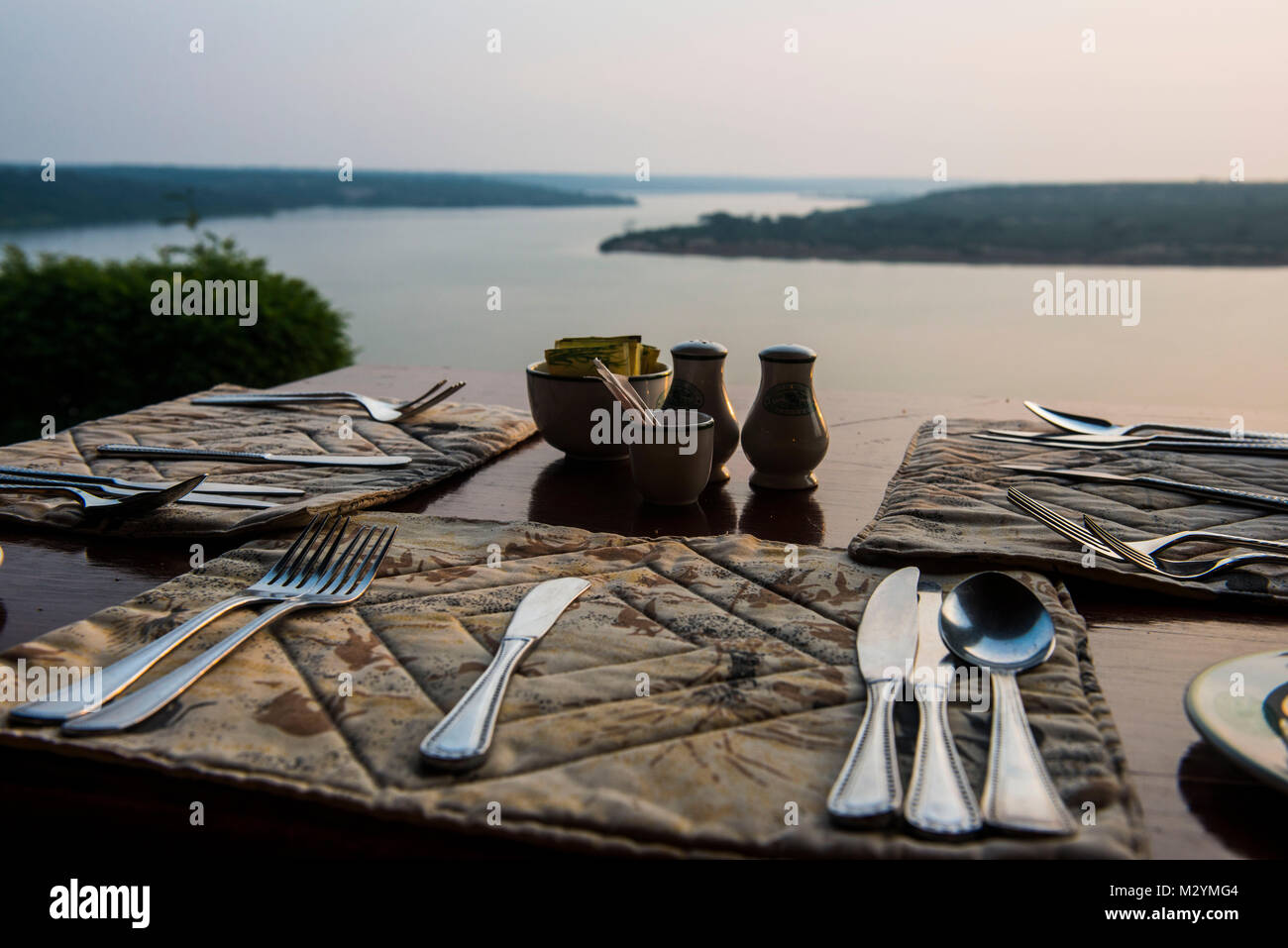 Ready set table in a restaurant above the Kazinga channel  linking lake george and lake Edward, Queen Elizabeth National Park, Uganda Stock Photo