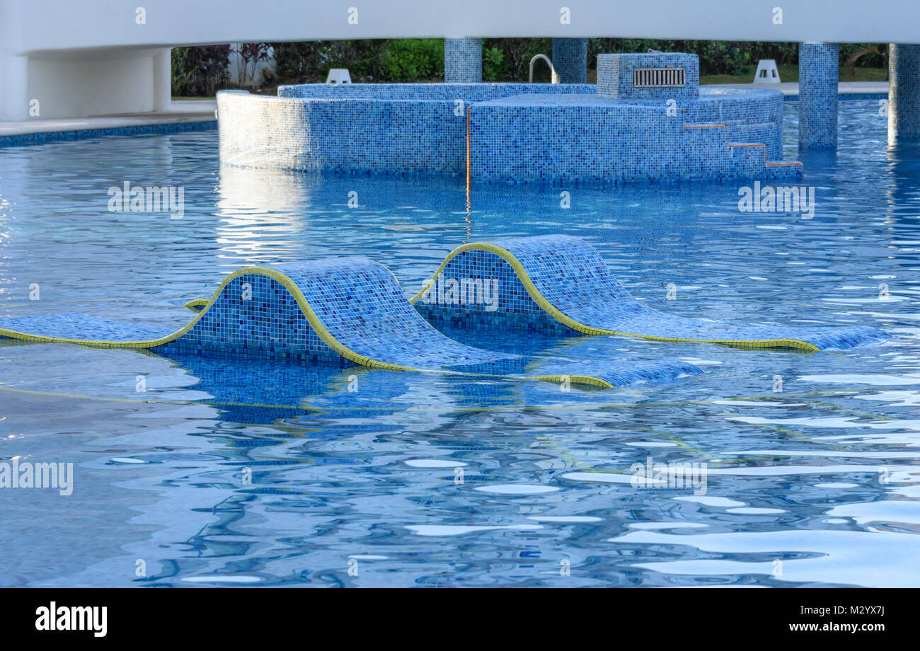 Chaise lounges in water. Swimming pool outdoors in Mexico. - Stock Image